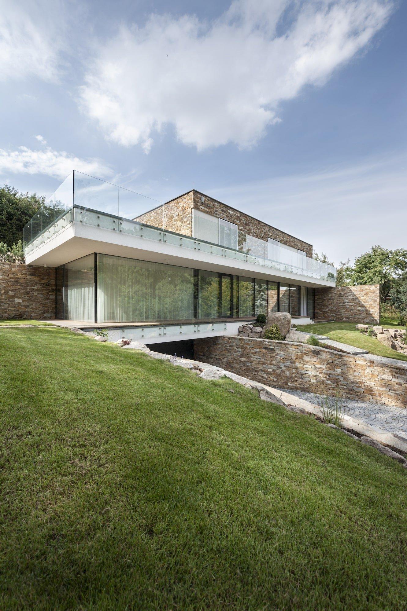 Rodinný dům byl postaven na z velké části zalesněném pozemku v blízkosti rybníka, který se nachází v otevřenější části parcely. Cílem projektu bylo vsadit hmotu nového domu do terénu tak, aby splynul s okolní zahradou a svahem.