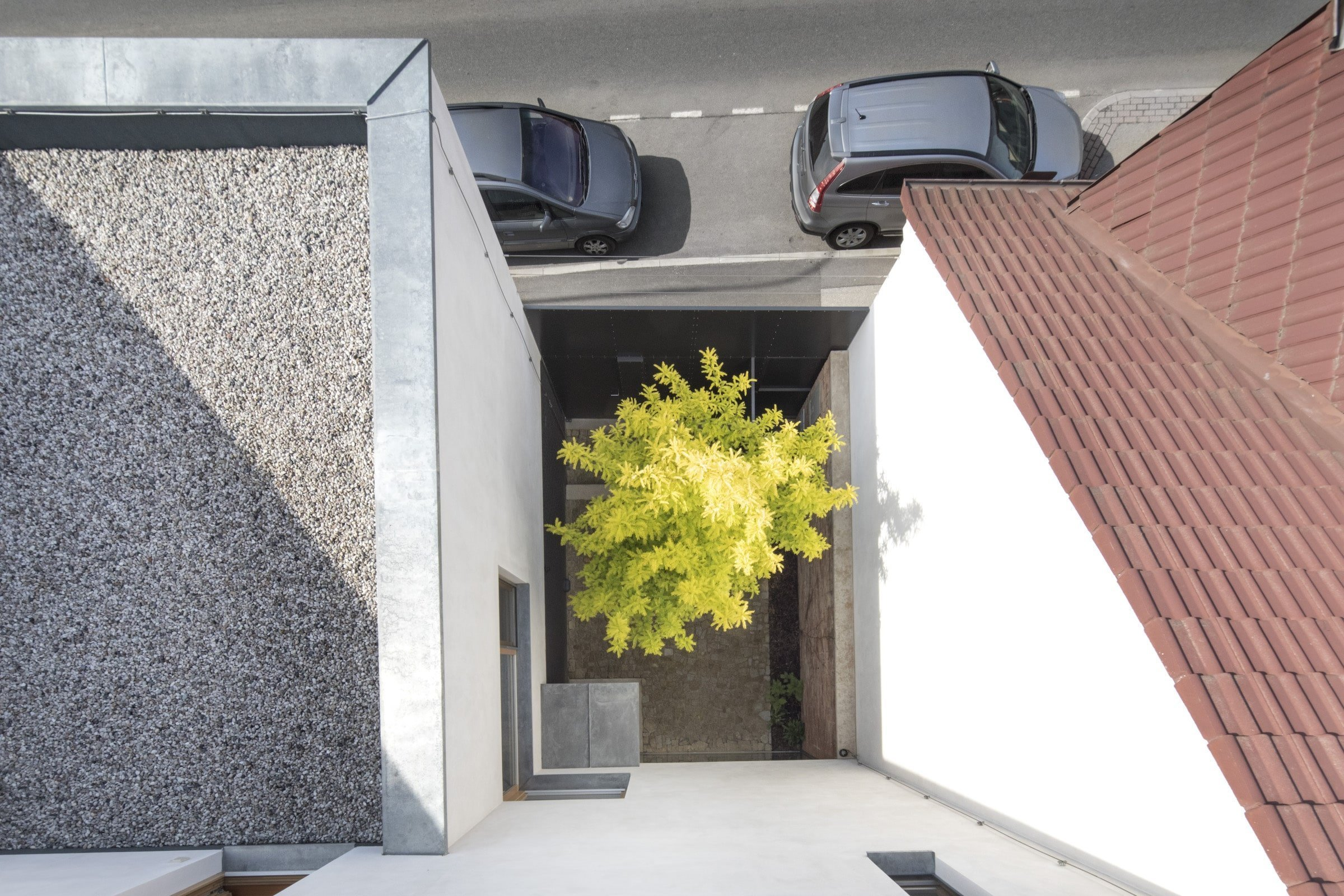 Architekti Hynek Holiš a Šárka Holišová Šochová vedou již několik let úspěšný ateliér v Praze. Dvojice hledala pozemek pro stavbu vlastního domu v okolí Benešova po dlouhá léta, kdy nakonec narazili na proluku nedaleko centra města. Dům, který zde byl postaven, navazuje na sousední řadové domy a přeci díky svému minimalistickému vzhledu vyniká.