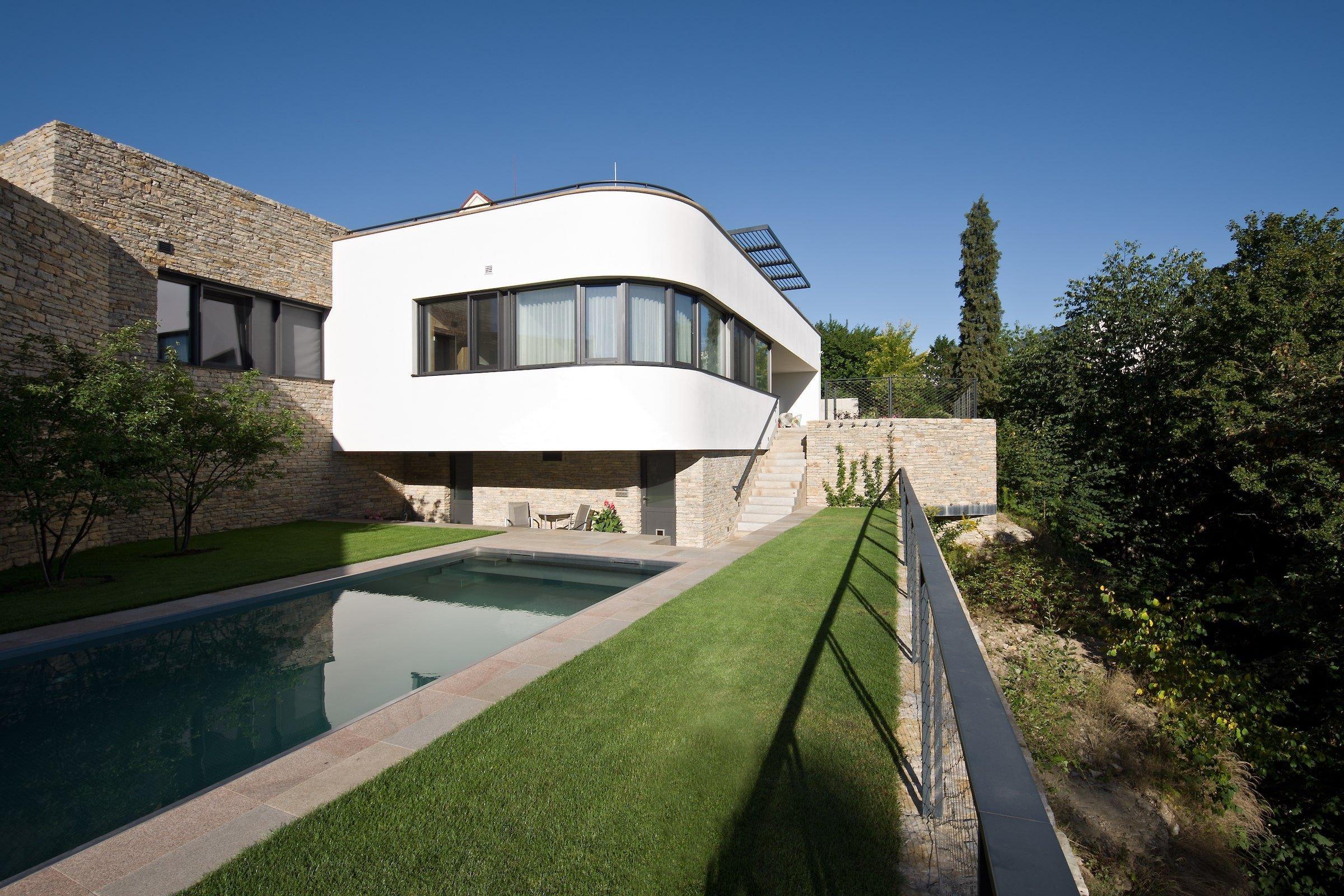 Krásný výhled do okolní krajiny a dostatečné soukromí se leckdy vyrovnají vyšší ceně za stavbu domu, jestliže se jedná o pozemek, na kterém je výstavba podstatně složitější a tím pádem i nákladnější – například kvůli svahu nebo celkové nerovinně. Jedním z projektů, kde se investice vyplatila, je tato funkcionalistická vila, která nadchne exteriérem i interiérem.