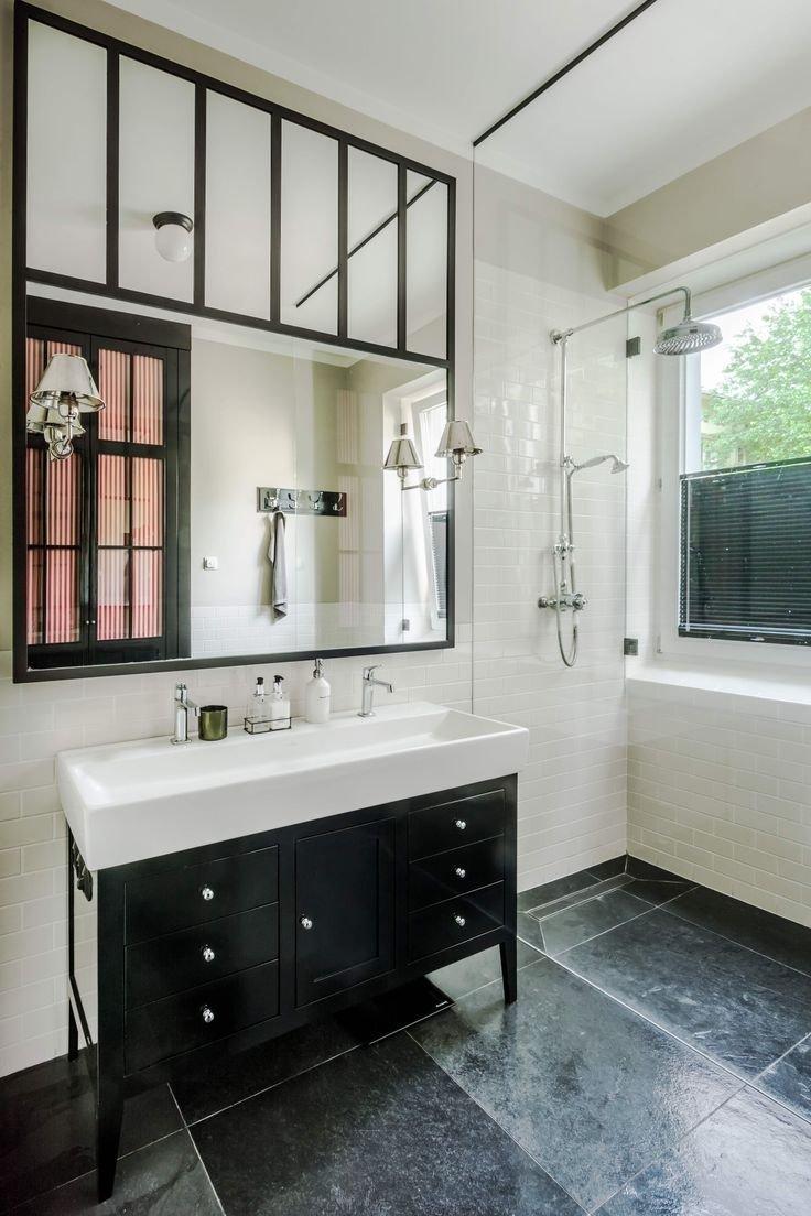 Obklad v koupelně je z drobných bílých dlaždic ve vysokém lesku.
