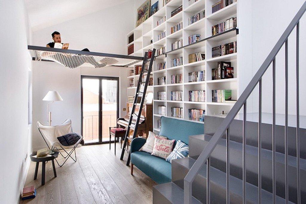 """Knížek není nidky dost! A i když máte malý byt, nemusíte se nijak omezovat. Bílé police opticky nechávají místnost dýchat a vytváří dojem prostornosti. Máte vyšší stropy? Tady máte inspiraci, jak lze prostor nad hlavou využít. Nenápadná síťka na první pohled nevadí a nijak nečiní místnost menší. Díky své výšce umožňuje pohodlně se procházet se vztyčenou hlavou a současně mít i svůj čtecí """"koutek""""."""