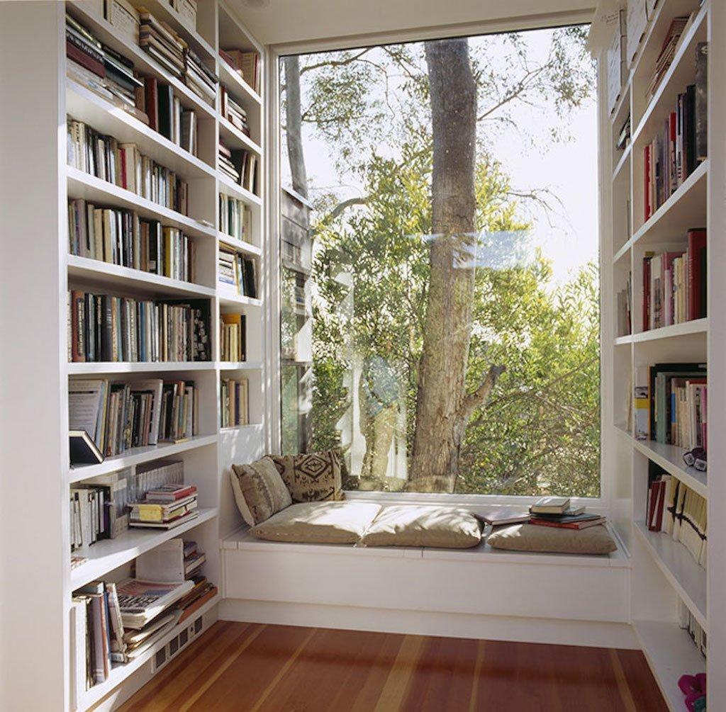 Denní světlo nenahradí žádná zářivka ani stolní lampa. V prostřed knih, přímo u okna s úžasným výhledem. Navodit si čtenářskou odpočinkovou atmosféru nikdy nebylo přirozenější a snazší. Užití bílého nábytku příjemně zesvětluje prostor a dodává mu neutrální čistou atmosféru. Nerozptyluje tak Vaši fantazii při čtení. Hnědá podlaha přitom dodává na pocitu tepla a s výhledem do stromů jen podporuje onen přirozený přírodní a čistý dojem.