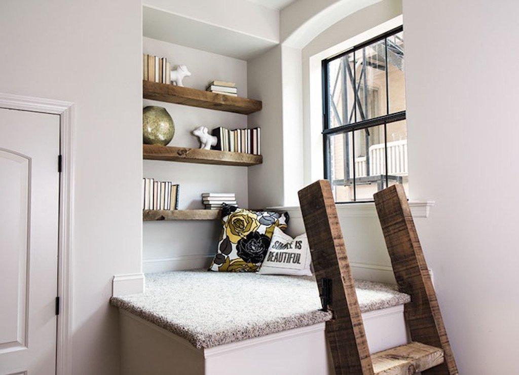 Pevný nábytek, vysoký sokl, skříň, … využít lze opravdu vše. Nejen že máte úložný prostor, ale současně i malou knihovničku s posezením. Čistý bílý koutek je decentně doplněn a zútulněn za pomoci dřevěných prvků - polic i žebříku. A i to malé okýnko má své využití. Dopřává čtenáři dostatek denního světla, ale i výhled ven.