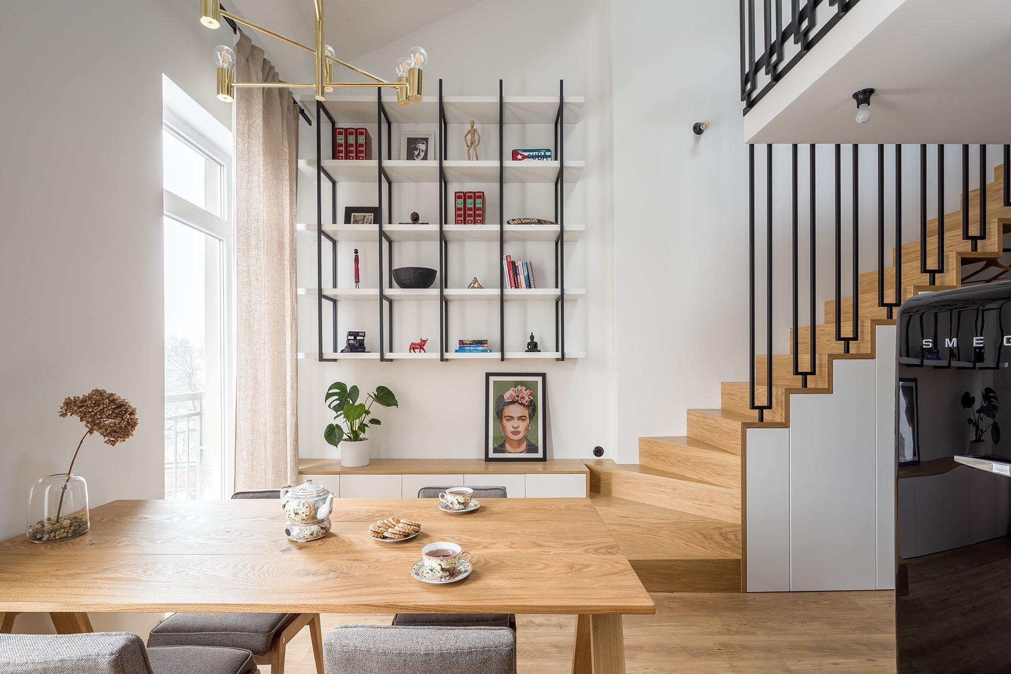 Naprosto úchvatný interiér v eklektickém stylu se nachází v malém, dvoupodlažním bytu činžovního domu v centrální části Polska. Pozornost si zaslouží nejen díky svému originálnímu vybavení, ale i zajímavým rozdělením funkčních zón. Standardně se totiž očekává, že v případě vícepodlažních domů nebo mezonetových bytů zaujímá obývací pokoj prostor ve spodním patře. V bytě v Lodži však architekti zvolili poněkud netradiční řešení.
