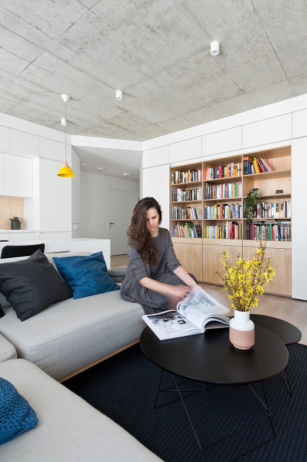 Tmavý koberec a konferenčnní stolek slouží jako kontrapunkt k ostatnímu světlému nábytku.