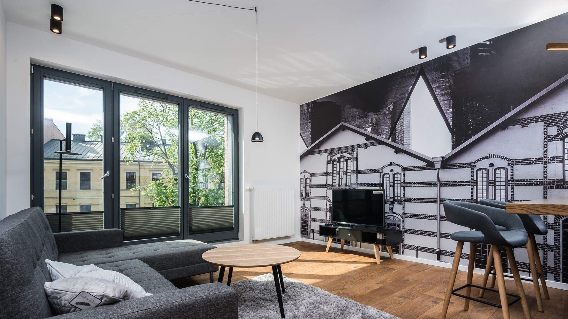 O tom, že šedá vůbec nemusí být nudná, svědčí tento komfortní byt v Krakově. V kombinaci s bílou výmalbou a hřejivým dřevem působí velice útulně a elegantně. K tomu dopomáhá světelný komfort interiéru, důraz na kvalitní materiály a minimalistický styl.