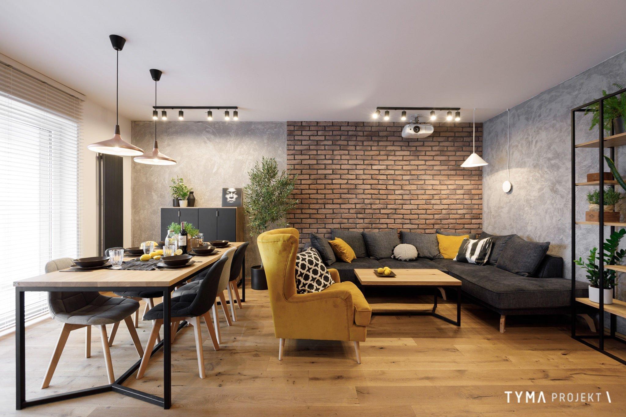 Prostor prvního bytu mladého páru je plný textur a vzorů. Od drsné betonové zdi, jemnost sametu na  nábytku nebo nepravidelnost kuchyňských dvířek. Byt se silnými barevnými akcenty medové, šedé a měděné.