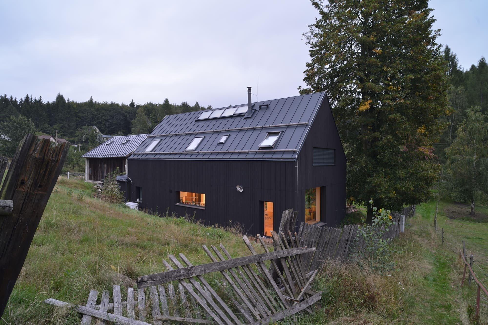 V malé osadě na severu Čech se zajímavě vyjímá černý dům posazený vedle stodoly. Tento nový rodinný dům dokončili na sklonku loňského roku profesionálové ze studia 3+1 architekti, kteří při realizaci vycházeli z původní stavby. Na tomto krásném pozemku střeženém vysokou lípou a zástupem slunečnic tak vzniklo originální bydlení plné světla a invence.