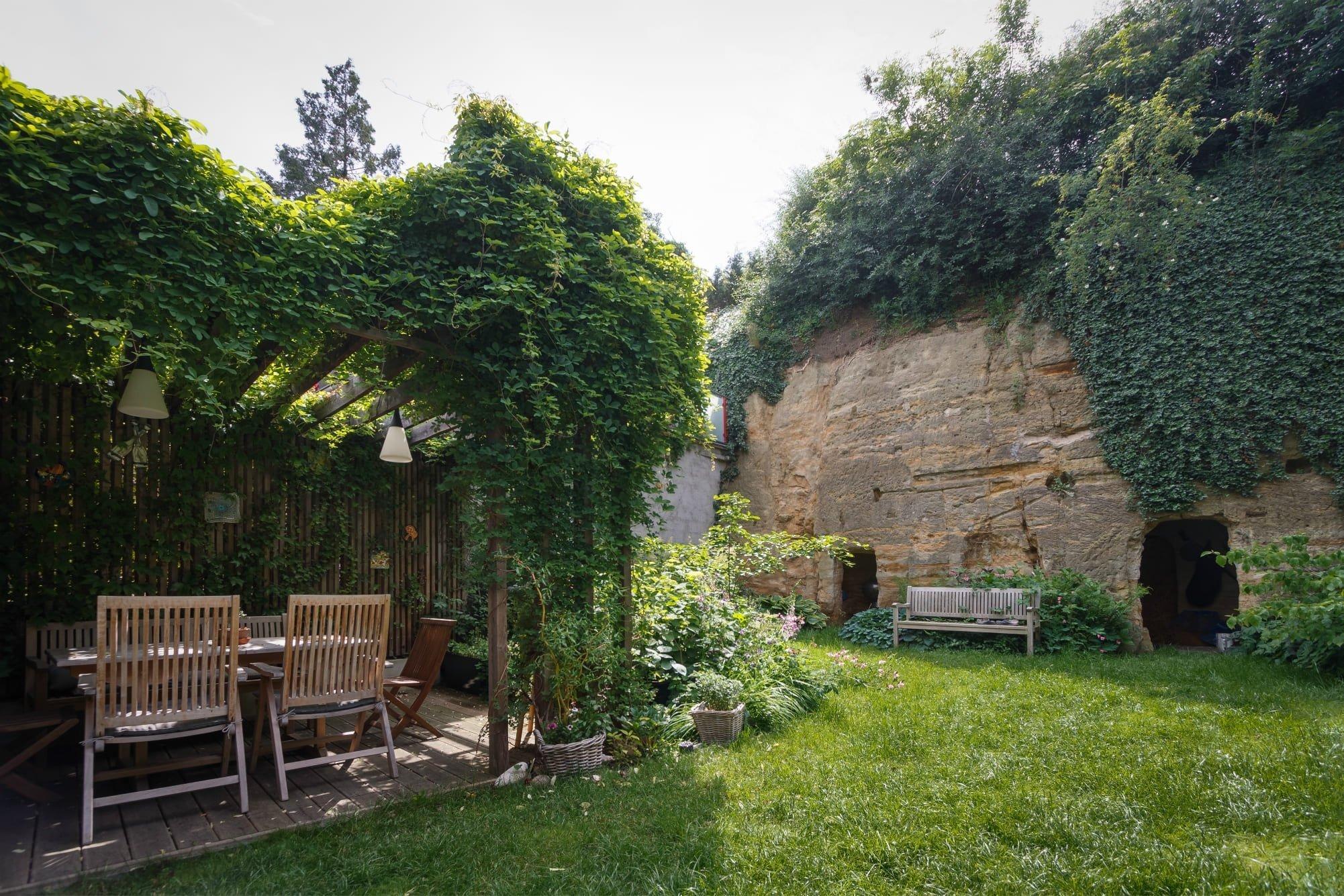 Oázou plnou zeleně zakončenou netradičním sklípkem oplývá přestavěný dům rozkládající se v jedné z pražských čtvrtí. Přestože na něj po stranách navazují další domy, nemusí se díky divoké přírodě kolem sebe cítit stěsnaně. Svobodomyslně si vymezuje svůj prostoj a dává najevo, že i dům v pražské čtvrti může být obklopen bujnou přírodou.