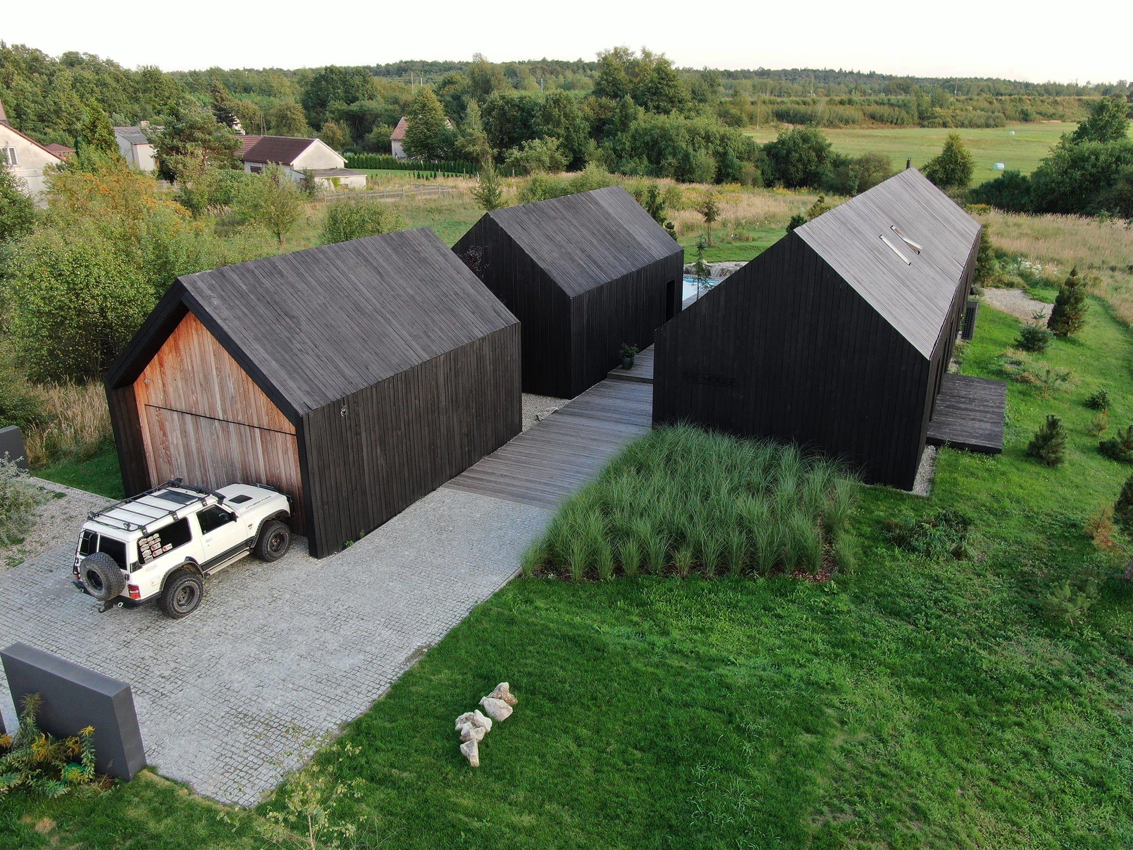 Nově postavené domy vypadají jako černé stodoly uprostřed pole. Ctí tradiční obdélníkový tvar se sedlovou střechou, ale nabízí mnohem víc. Jejich výjimečnost potvrzuje i fakt, že byly nominovány na cenu za architekturu.