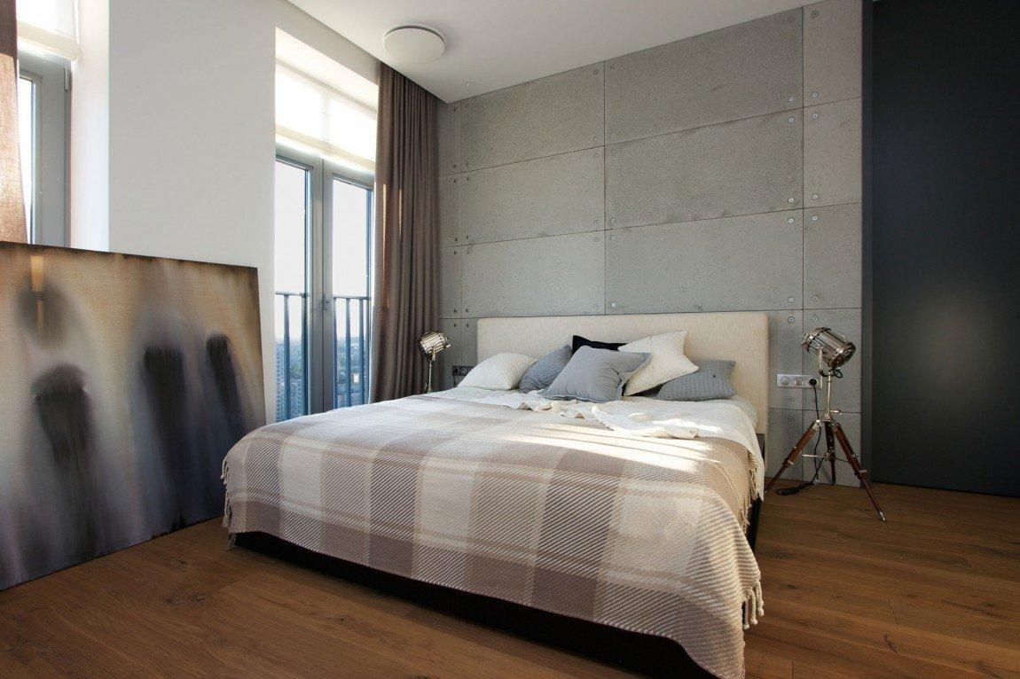 Betonové panely za postelí evokují industriální vzhled.