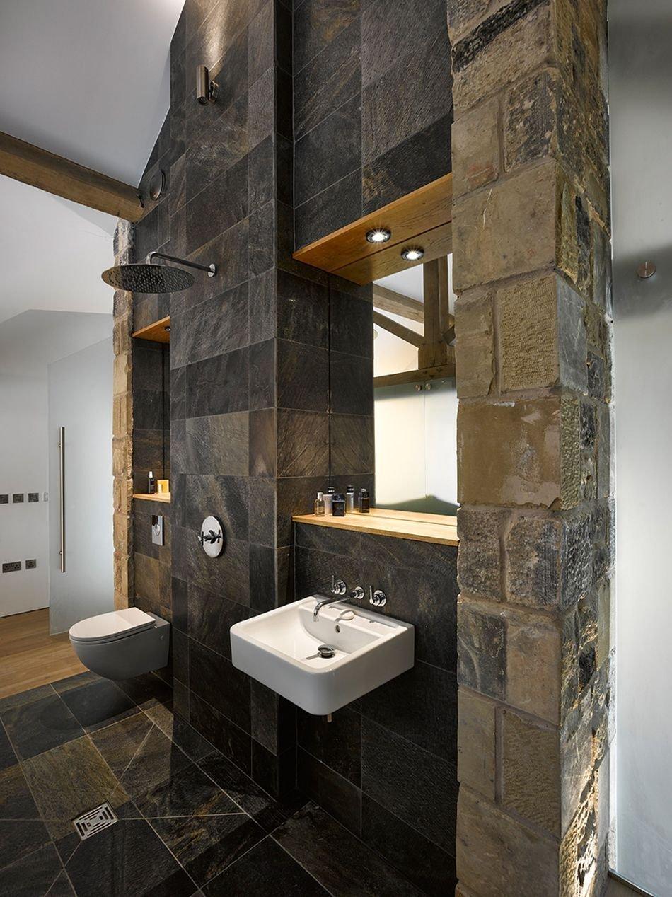 """Otevřený sprchový """"kout"""" je moderní, kamenný obklad navazuje na původní účel budovy."""