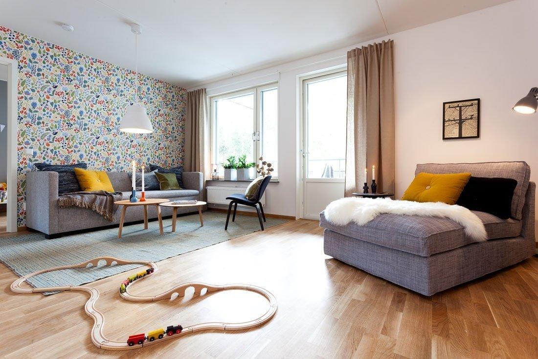Veselá tapeta s drobným vzorem je dobrou volbou. Také barevné polštáře pokoj rozzáří.