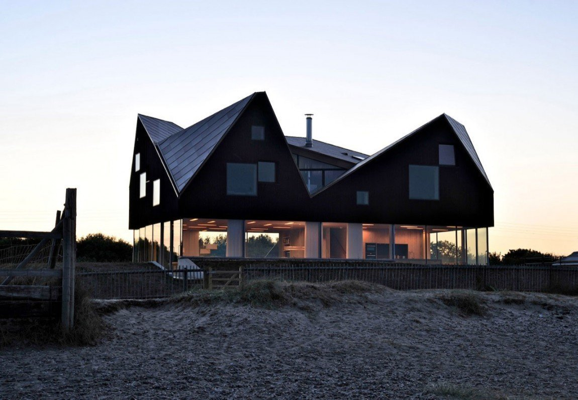 Tento dům na sebe zbytečně nepoutá pozornost, i když je výjimečný. Z dálky se dokonce zdá, že se jedná o obyčejný pobřežní domek, napůl schovaný v písečné duně. Ovšem stačí se kousek přiblížit, a s údivem si uvědomíte, že dům má pod sebou ještě skleněné přízemí, které vkusně splývá s okolím.