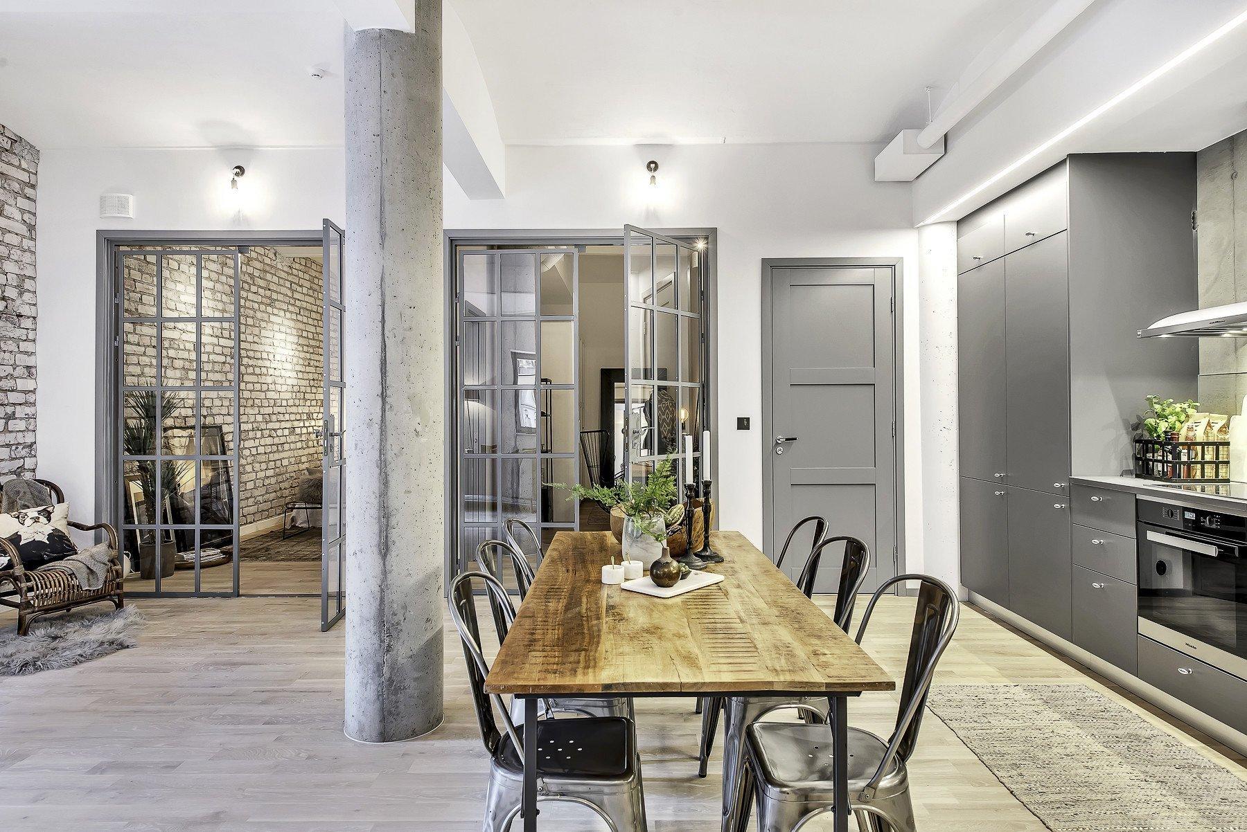 Tento romantický industriální podkrovní byt funguje souhrou různorodých užitých materiálů a stavebních prvků – ať už jsou to betonové stěny, dřevo, omítnuté cihly, klenutý strop či ocelové rámy u skleněných oken a dveří. Kombinace toho všeho vyvolává dojem příjemného a útulného prosvětleného prostoru. Mísí se tu teplé interiérové prvky (dřevěná deska stolu, proutěné křeslo, stolička) se studenou průmyslovostí (betonové stěny, ocelové rámy).