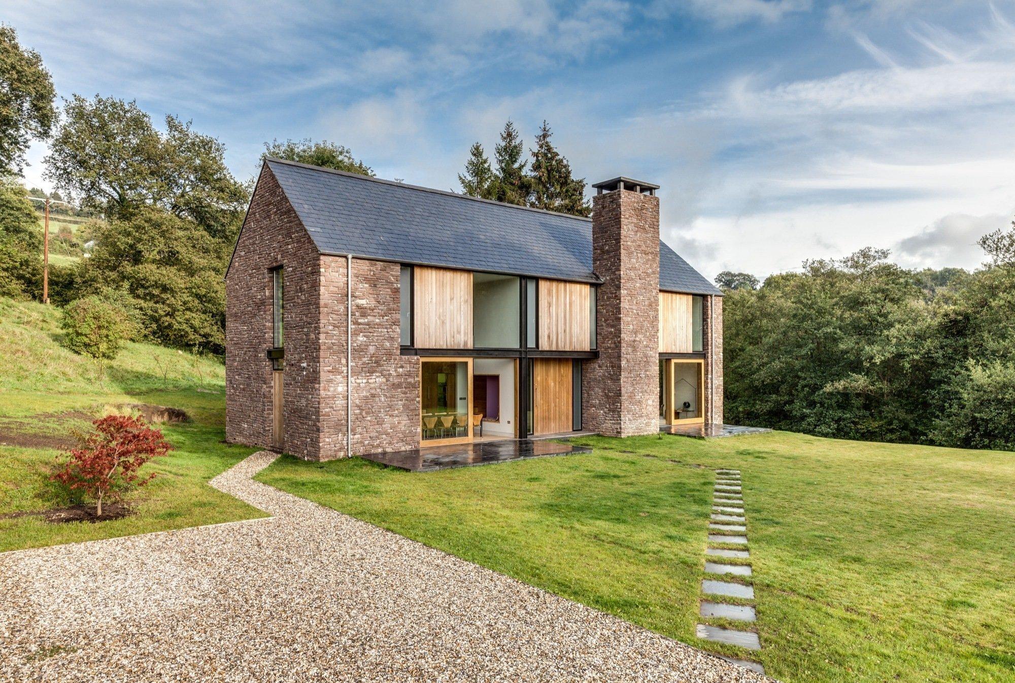Do pískovce oděný vesnický rodinný dům ležící v odlehlém údolí v Monmouthshire ve Walesu navržený architekty Martinem Hallem a Kelly Bednarczykem vzdává svým vzhledem poctu velšské lidové stodole.
