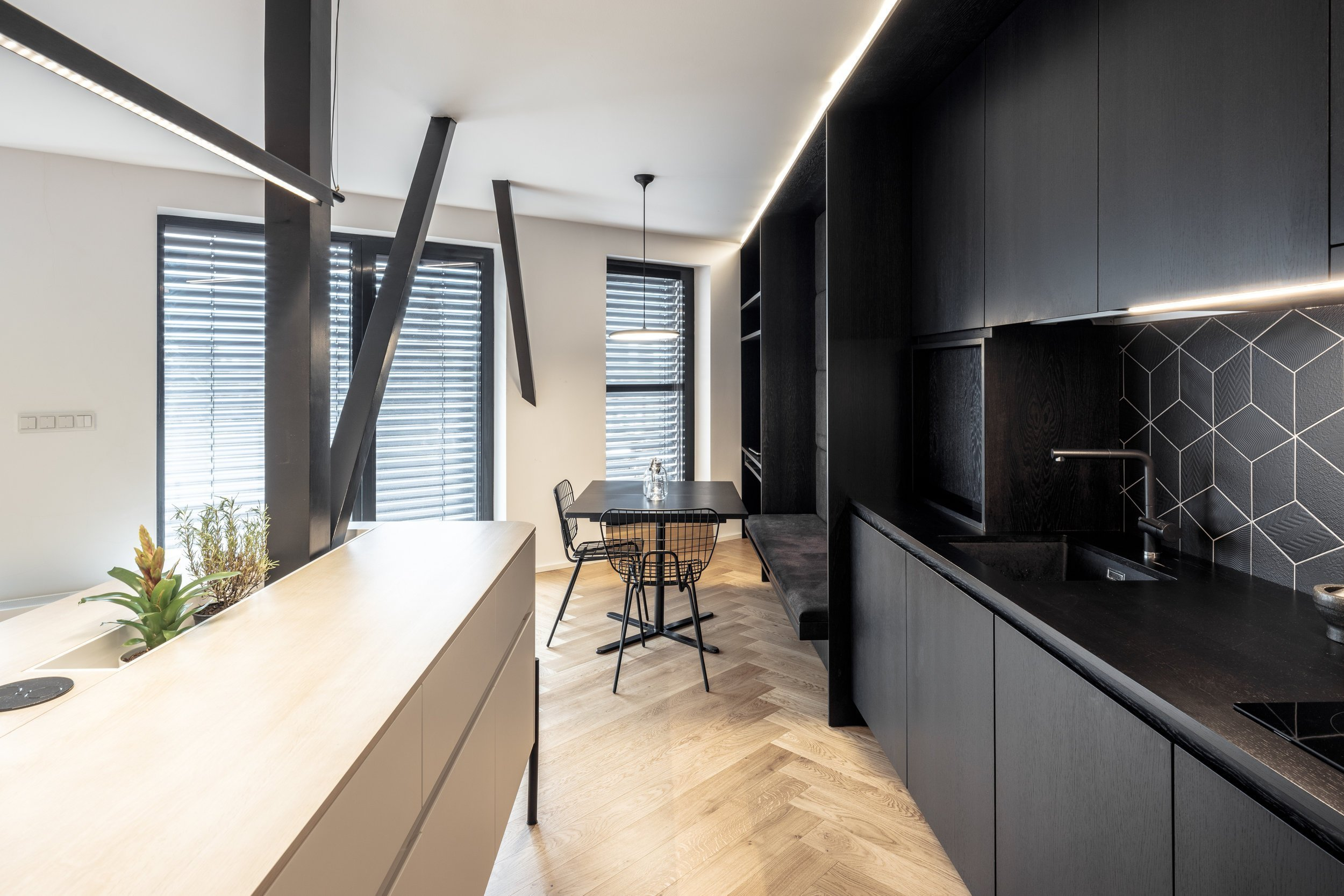Otevřený obytný prostor. Absence klasických chodeb. Sloupy jako součást zařízení interiéru. Na ploše téměř sto metrů čtverečních vznikl funkční a řemeslně dotažený byt. Příjemným bonusem je rozsáhlá střešní terasa a výhledy z obytných místností.
