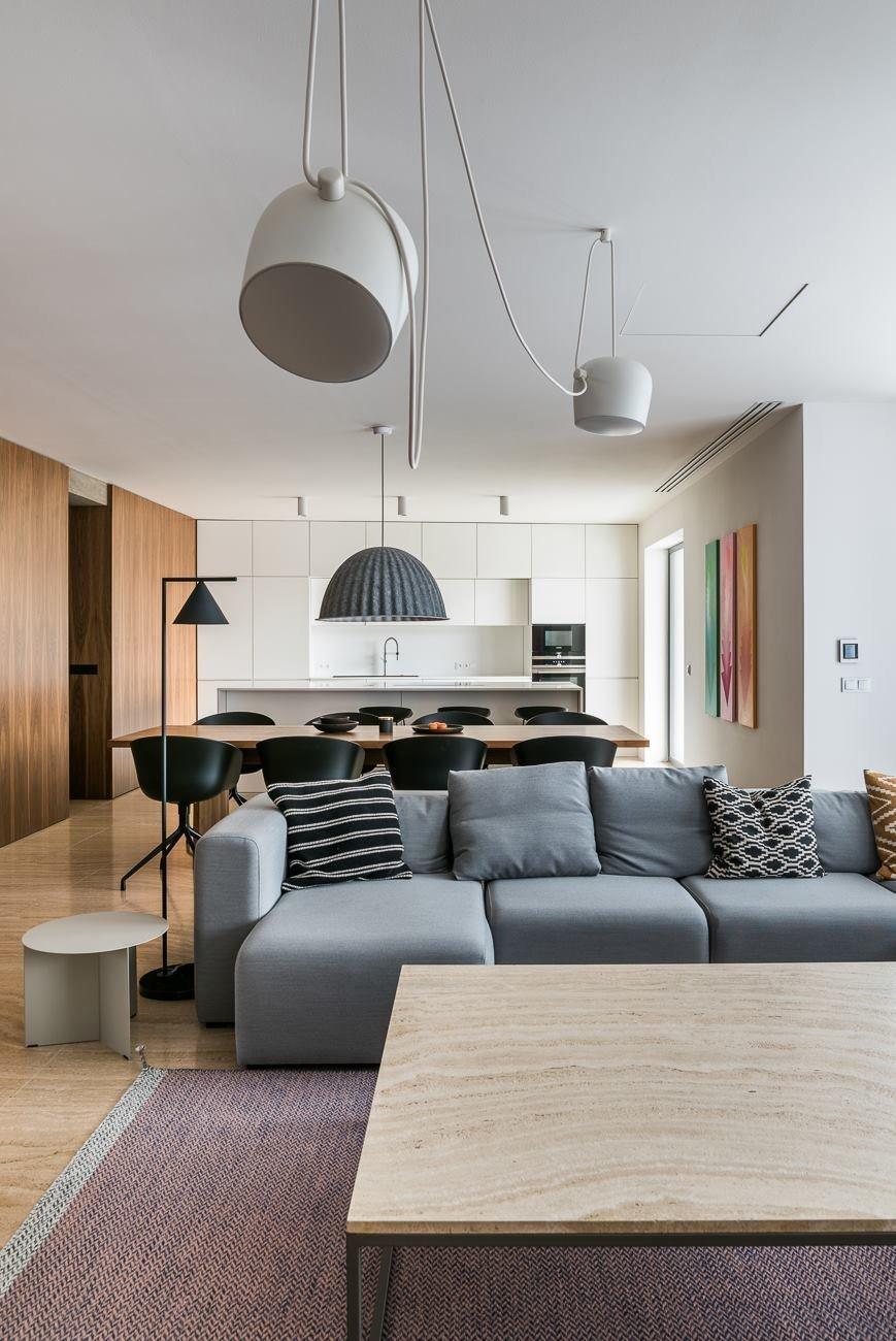 Velký prostorný byt, světlý interiér. Bílá barva, přírodní dřevo a travertin. Vše zázemí je důsledně integrované, zůstává pouze čistý obytný prostor, nic víc.