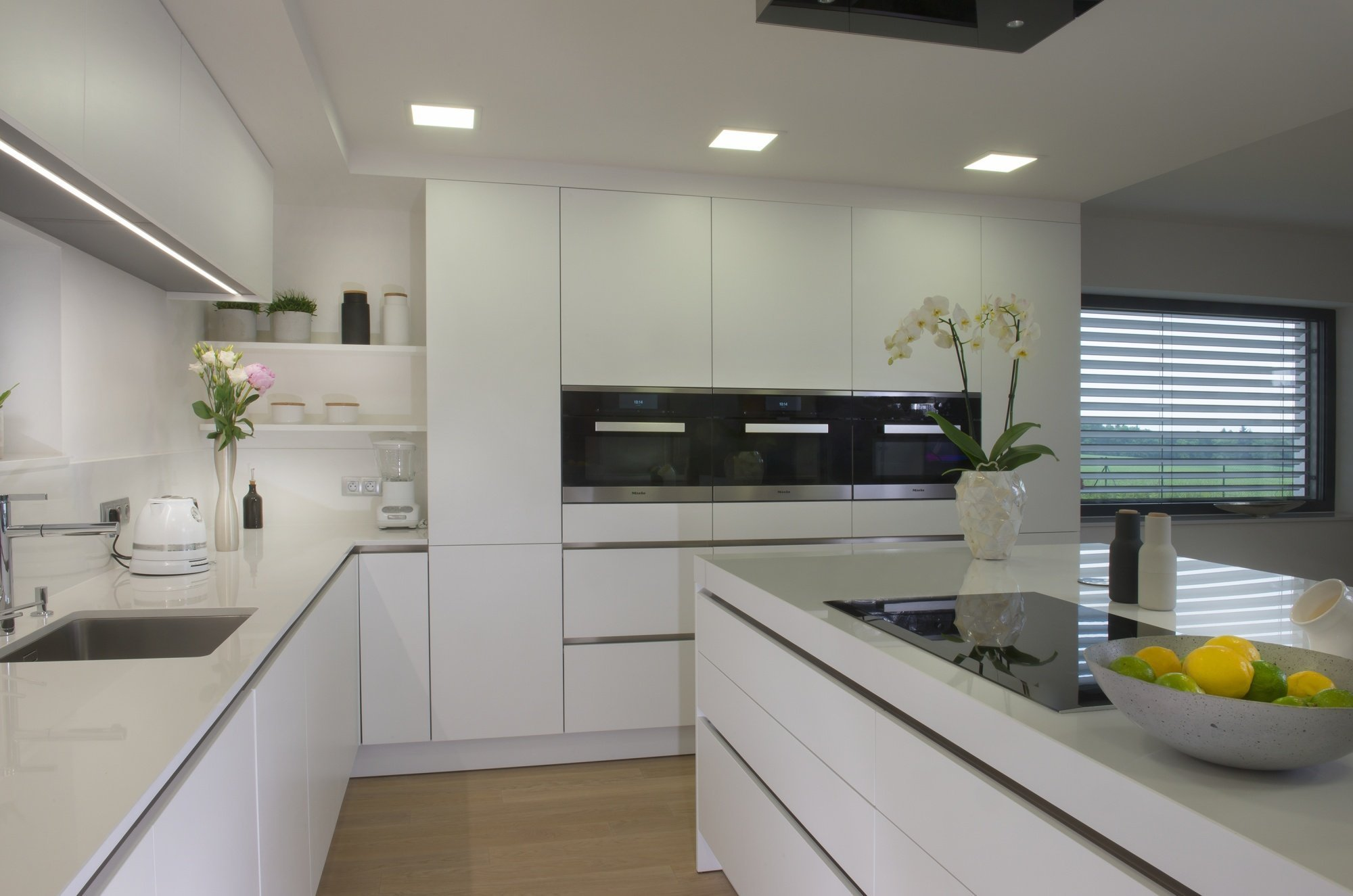 Kuchyň EGGERSMANN, rodinný dům. Provedení matný strukturovaný lak 539 Blutenweiss, bezúchytkový systém e:sing - lišty nerez . Pracovní deska je Technistone…