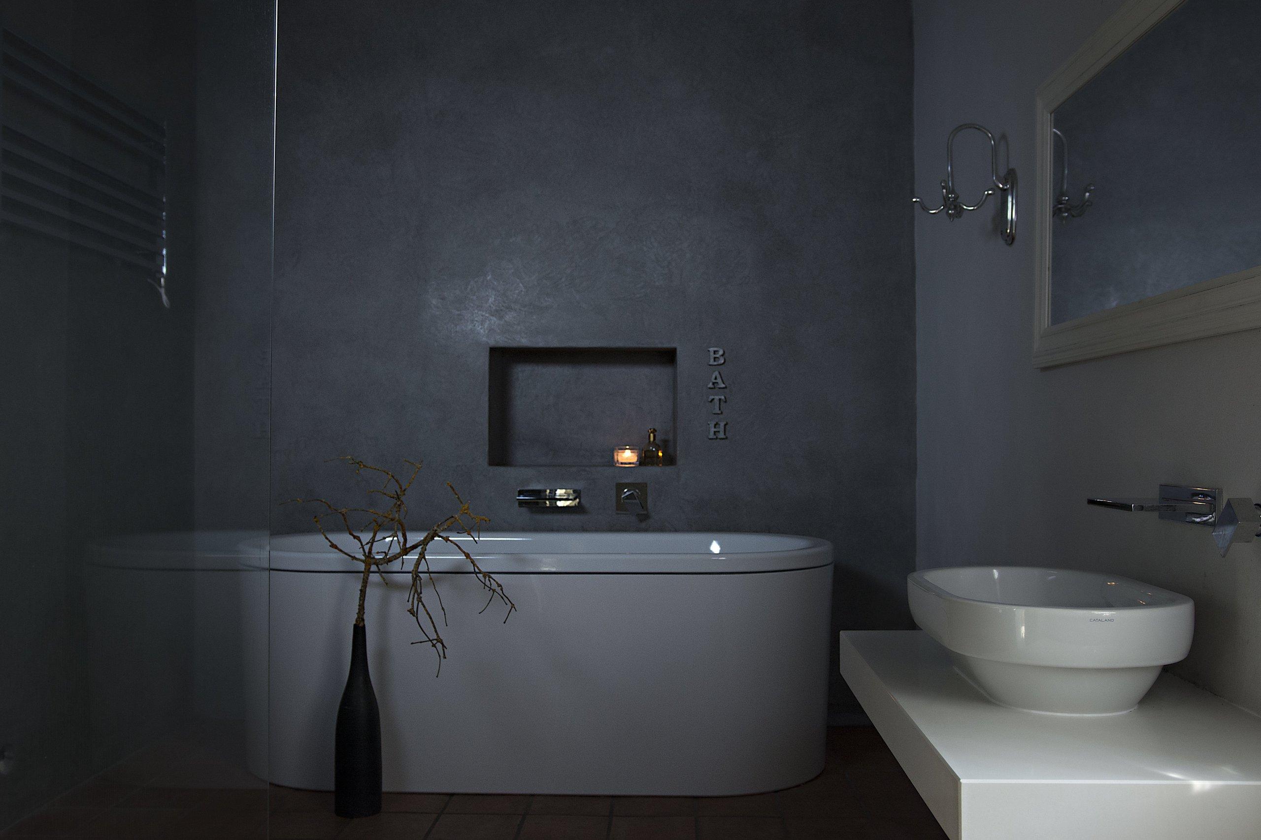 Koupelna s marockým štukem, prostornou vanou a vlevo sprchovým koutem odděleným skleněnou stěnou.