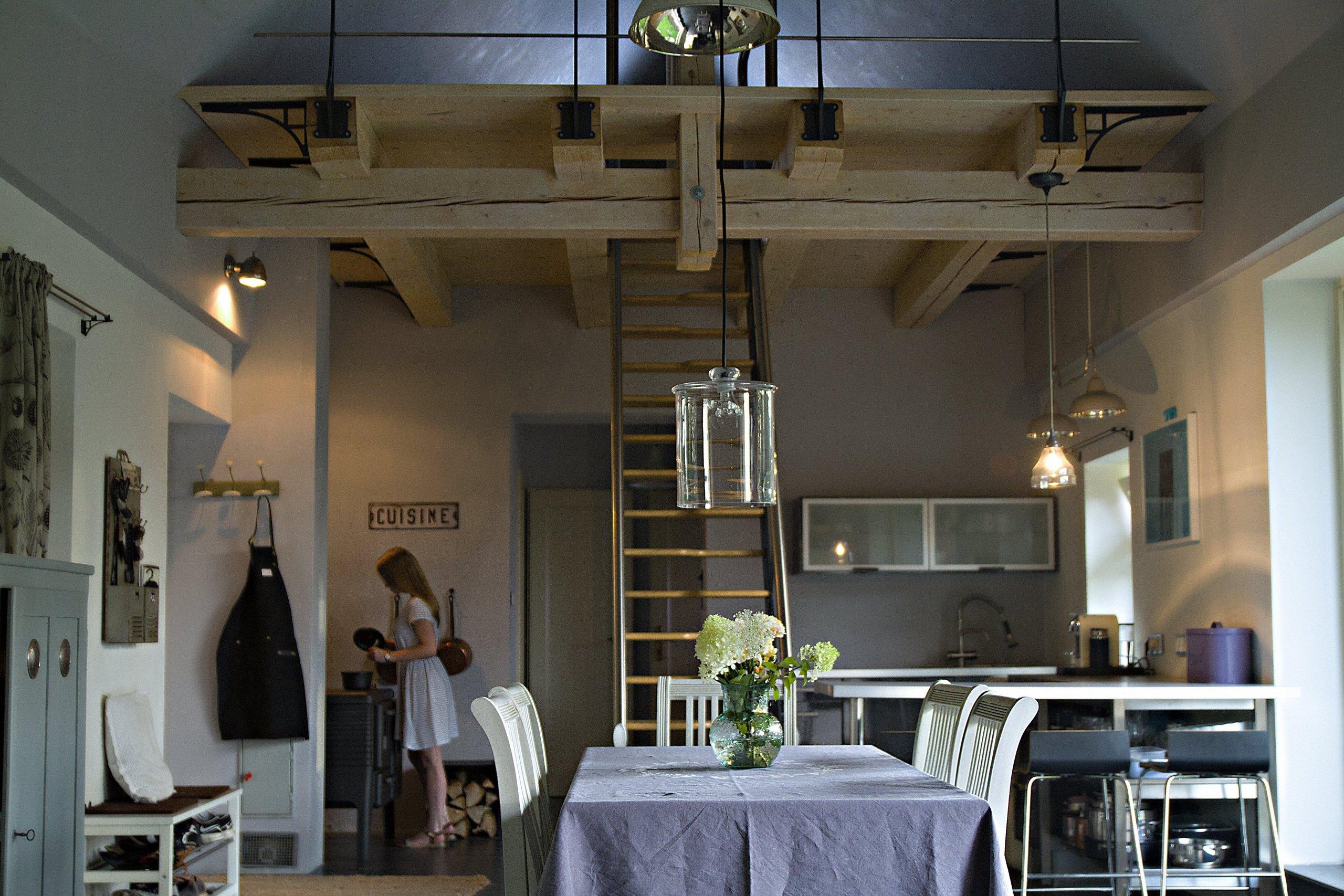 Pohled z druhé strany na jídelnu a kuchyni s litinovým sporáčkem. Po mlynářských schodech se dostanete do podkroví, kde je prostor pro hosty.