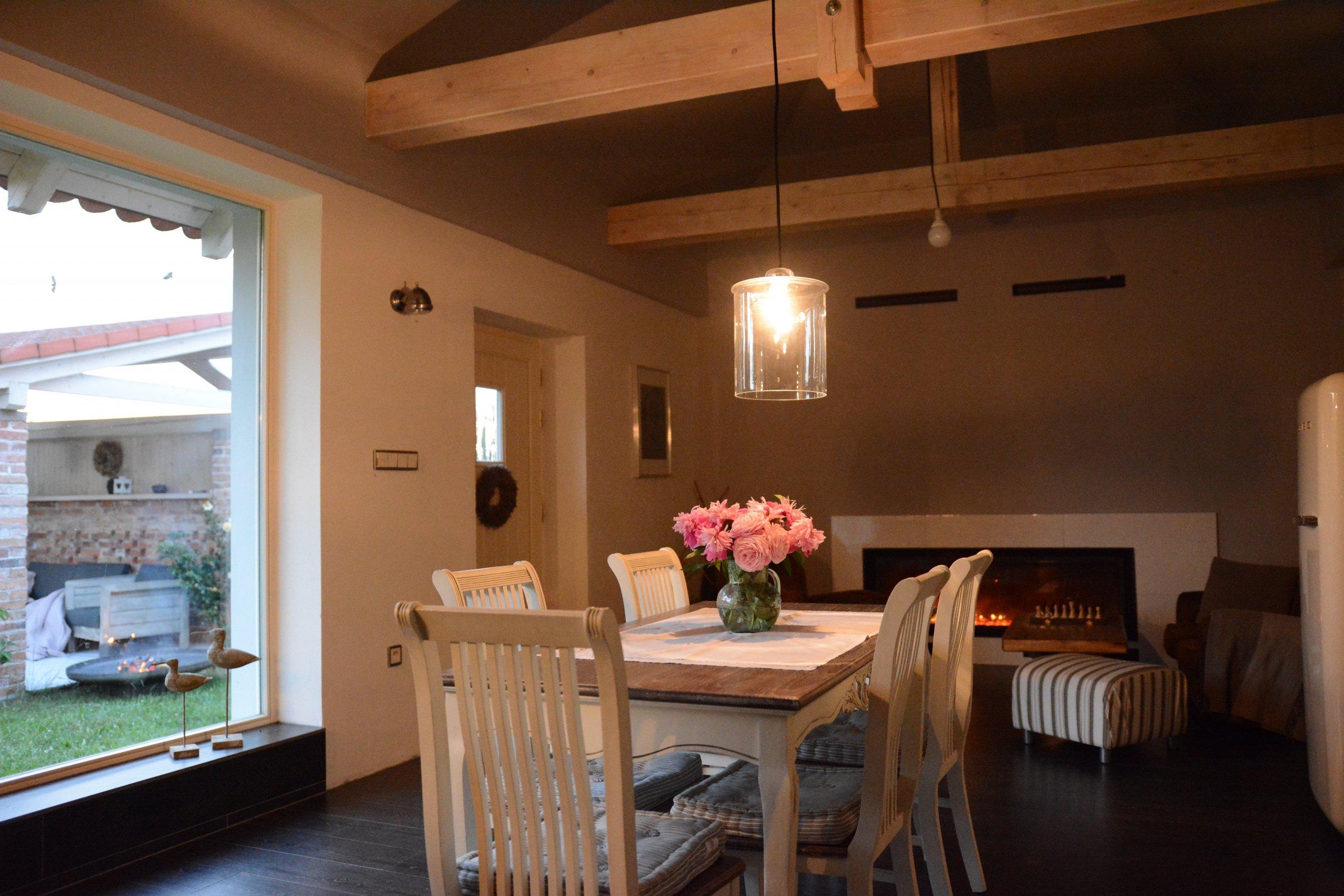 Jídelna a obývák v jednom k posezení a výhledem skrz velké francouzské okno.