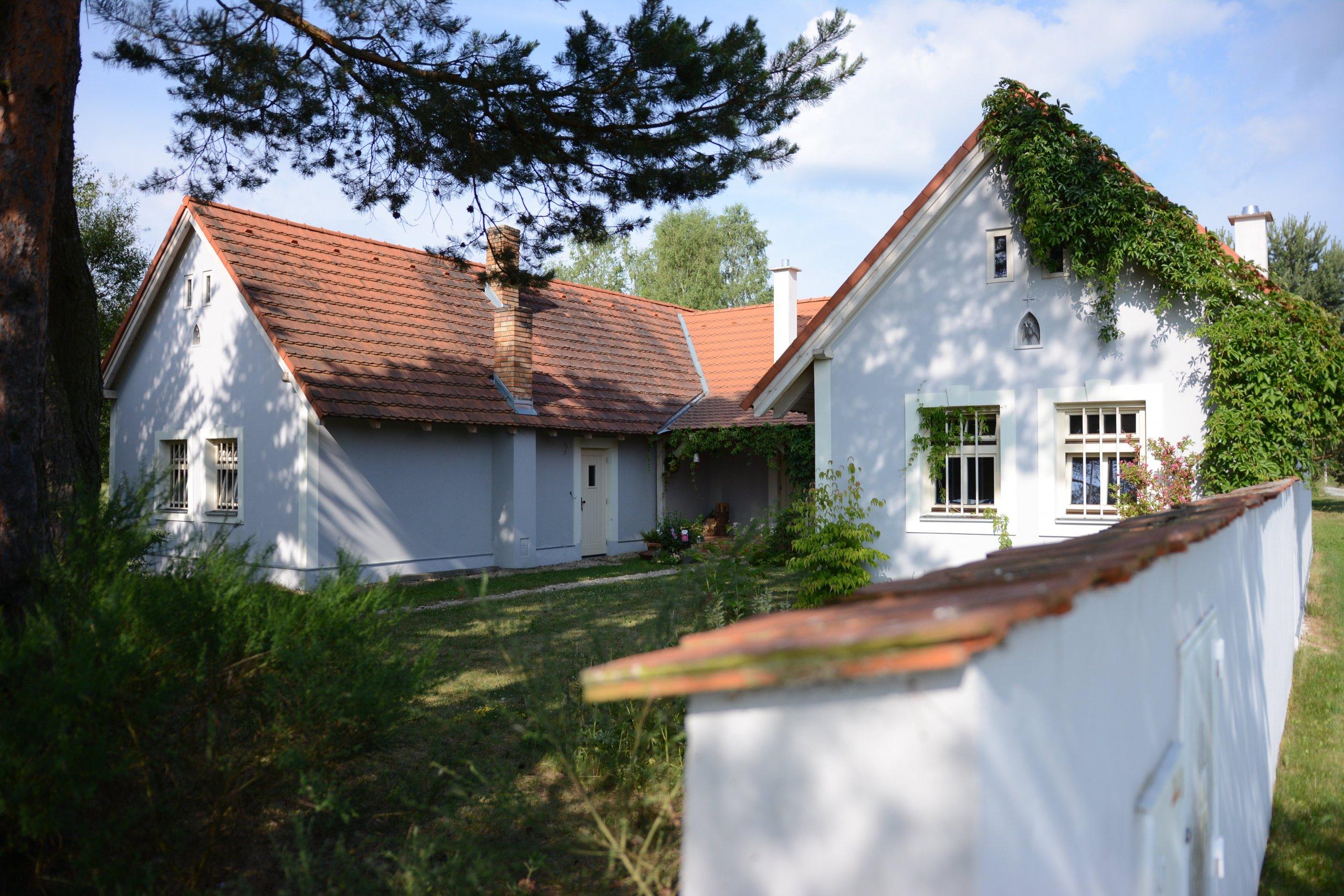 Klasické jihočeské stavení ve tvaru U s šedo-bílou omítkou a klasickými okny.