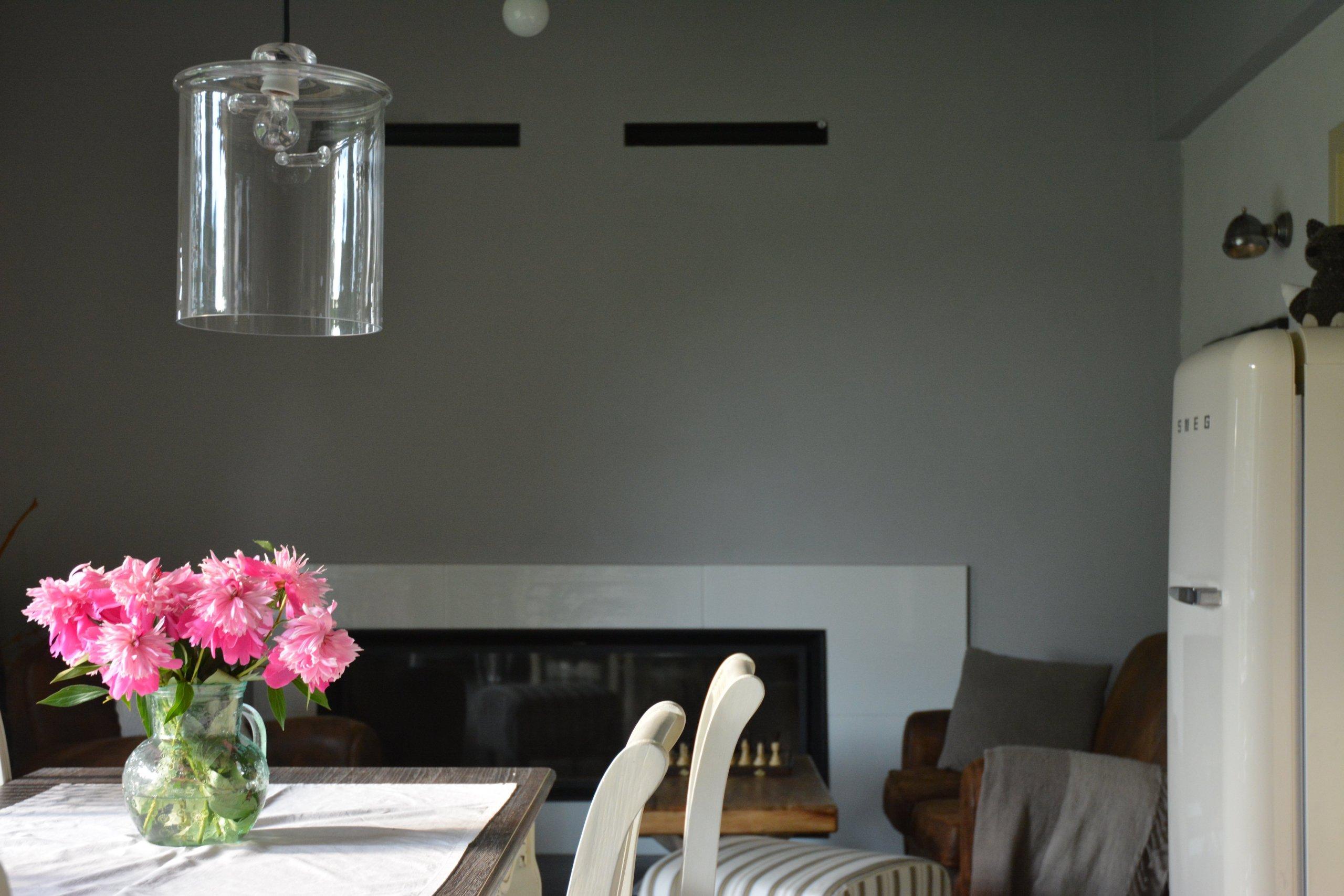 Detail na na obýváková kout s koženou sedačkou a krbem s panoramatickým prosklením.