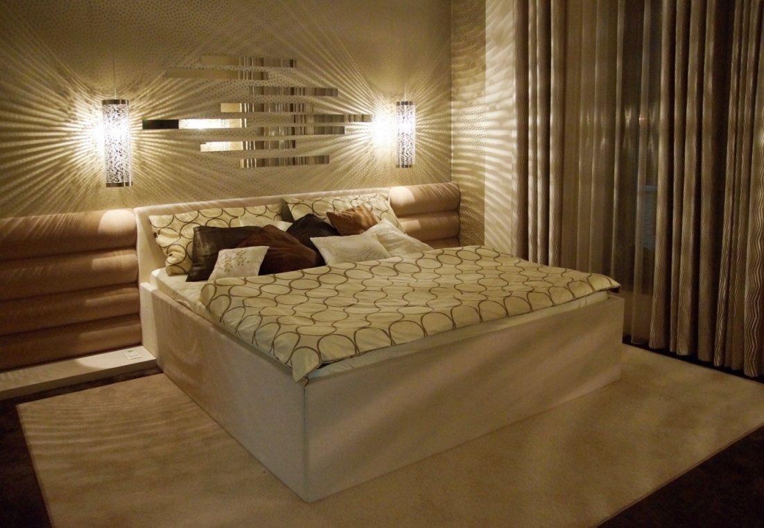 Osobitá ložnice pro podnikavé manžele s využitím akcentů různé běžové, lesku a matu a různých povrchů.