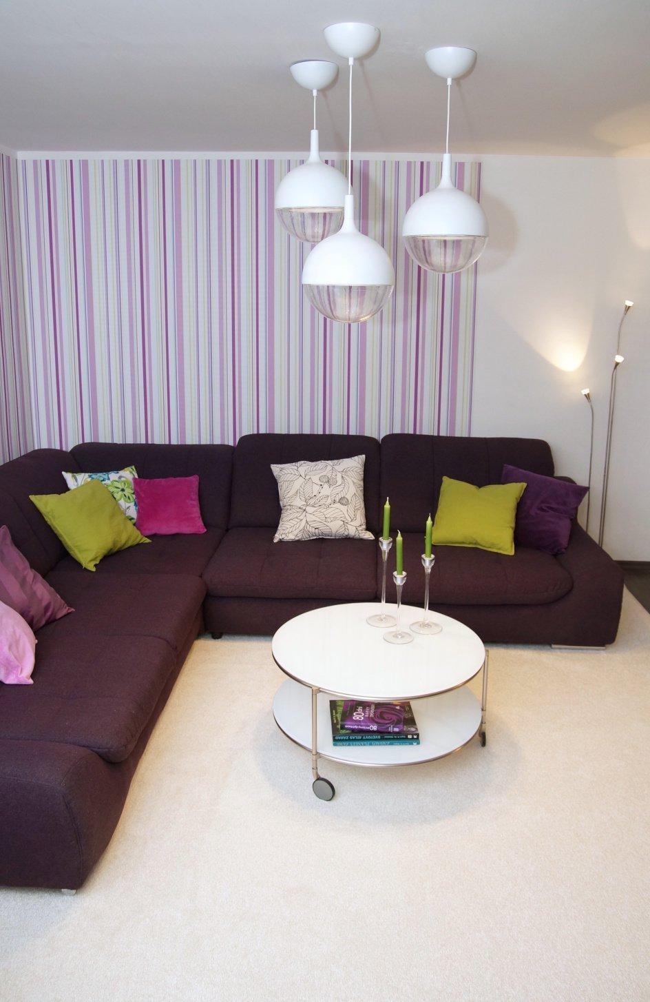 Obývací pokoj s krbem s fialovou sedačkou
