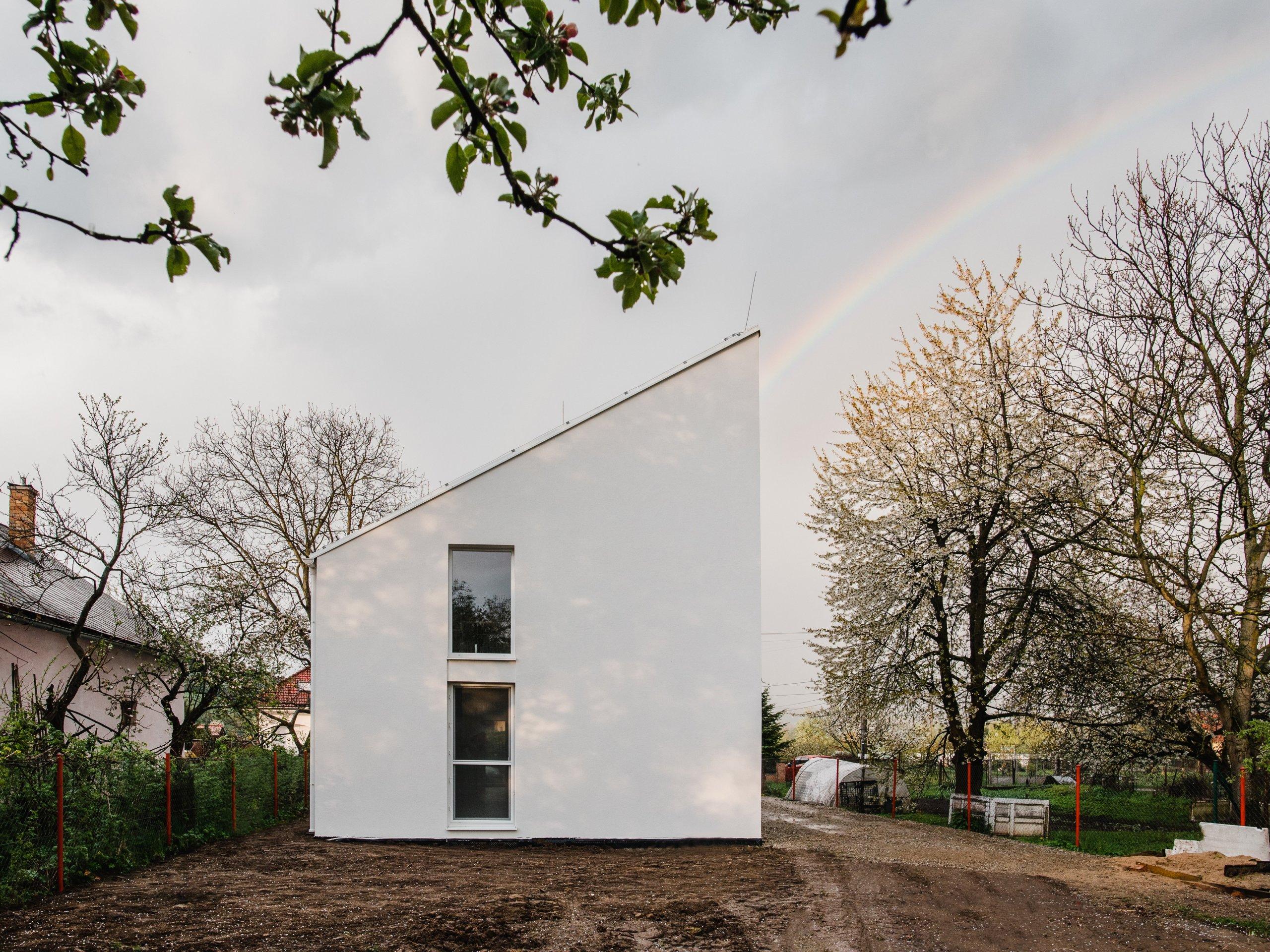 """Nízky rozpočet, úzky pozemok a na ňom plnohodnotný štvorizbovýrodinný dom. """"The Half House"""" je v tvare polovice domu so sedlovou strechou.…"""