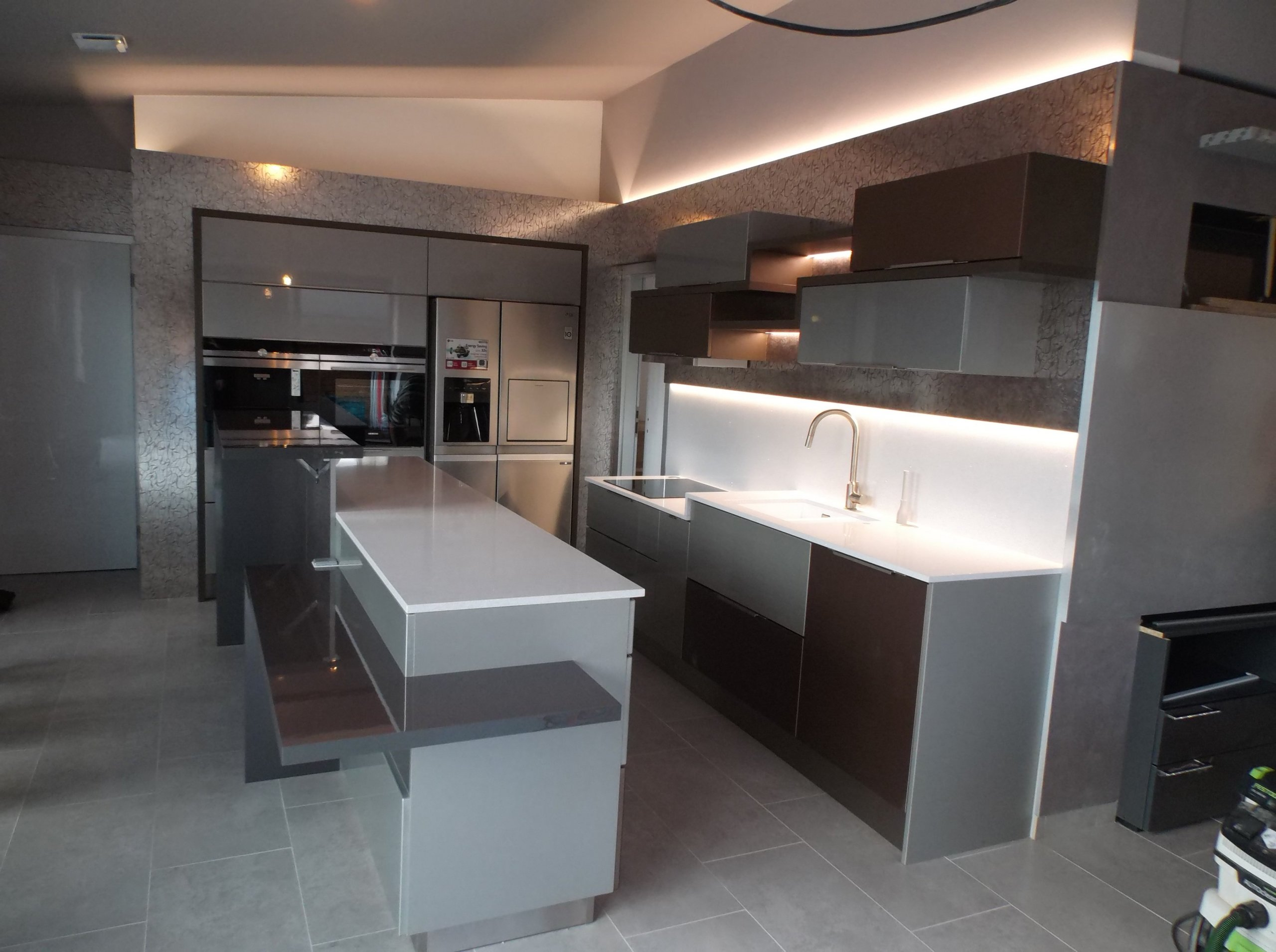 Kuchyně je v kombinaci bílá, metalická šedohnědá s bílou kamennou deskou, led osvětlením,  pro ozvláštnění je použita metalická SIBU folie.