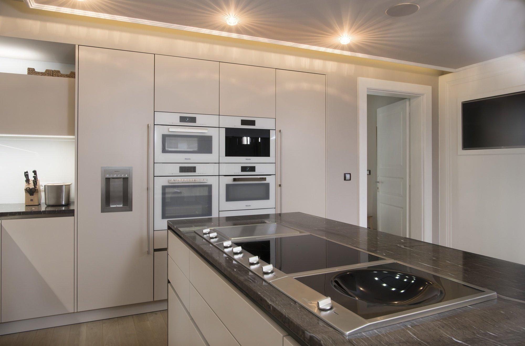 Kuchyň EGGERSMANN - provedení je matný strukturovaný lak Anconna 537 Toffe, bezúcyhtkový systém nerez, doplňky Dornbracht. Pracovní deska je žula Brown silk…