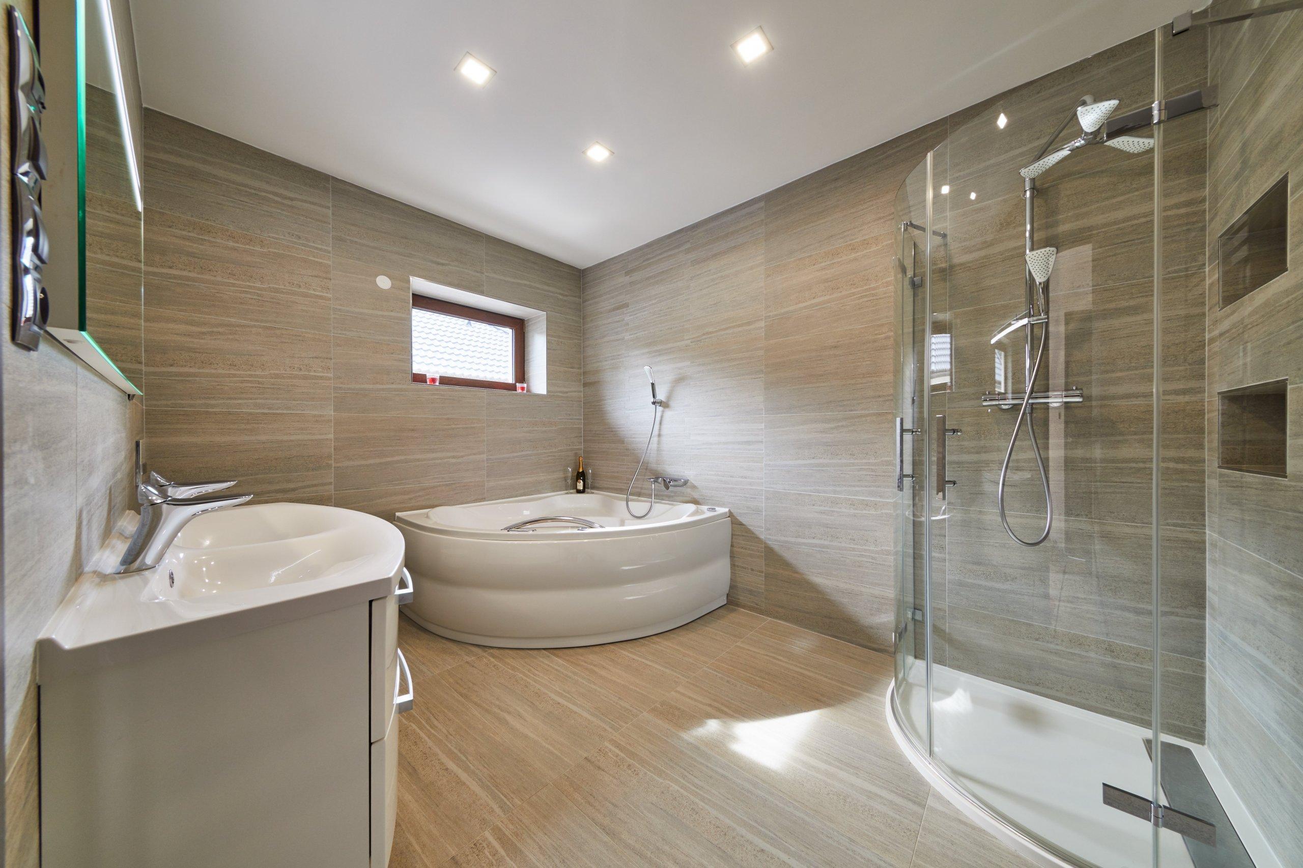 Velmi prostorná koupelna s velkoformátovými obklady a dlažbou od italského vyrobce ABK. V prostoru se se opakuje oválný tvar u hydromasážní vany, sprchového…