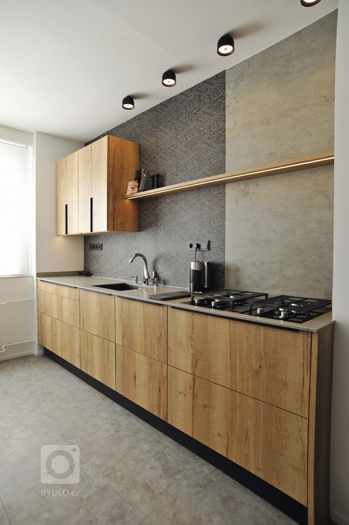 Realizace kuchyně ve skandinávském stylu. Schüller Cremona – imitace dub v kombinaci s matným sklem. Pracovní deska z keramiky, obklad z řezané mozaiky v…