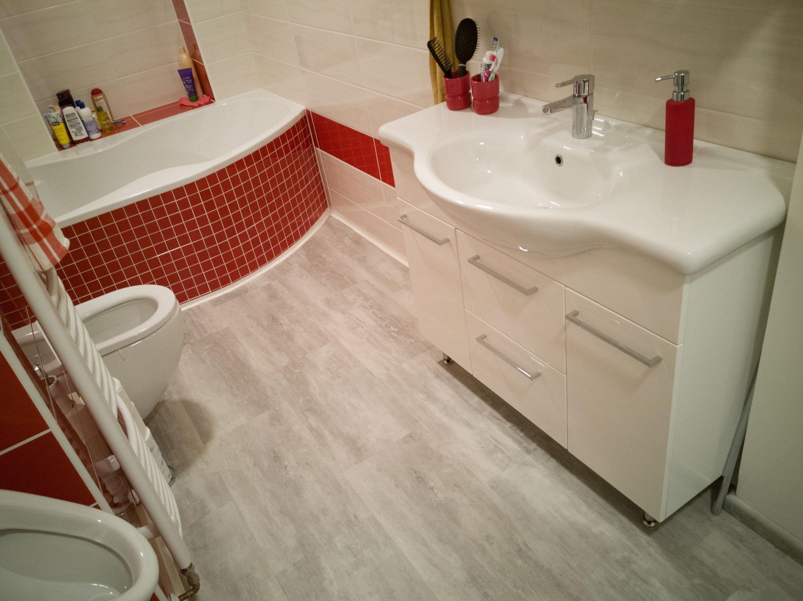 Barevně hezky sladěná koupelna. Obklady z keramické dlažby jsou doplněny vinylovou podlahou.