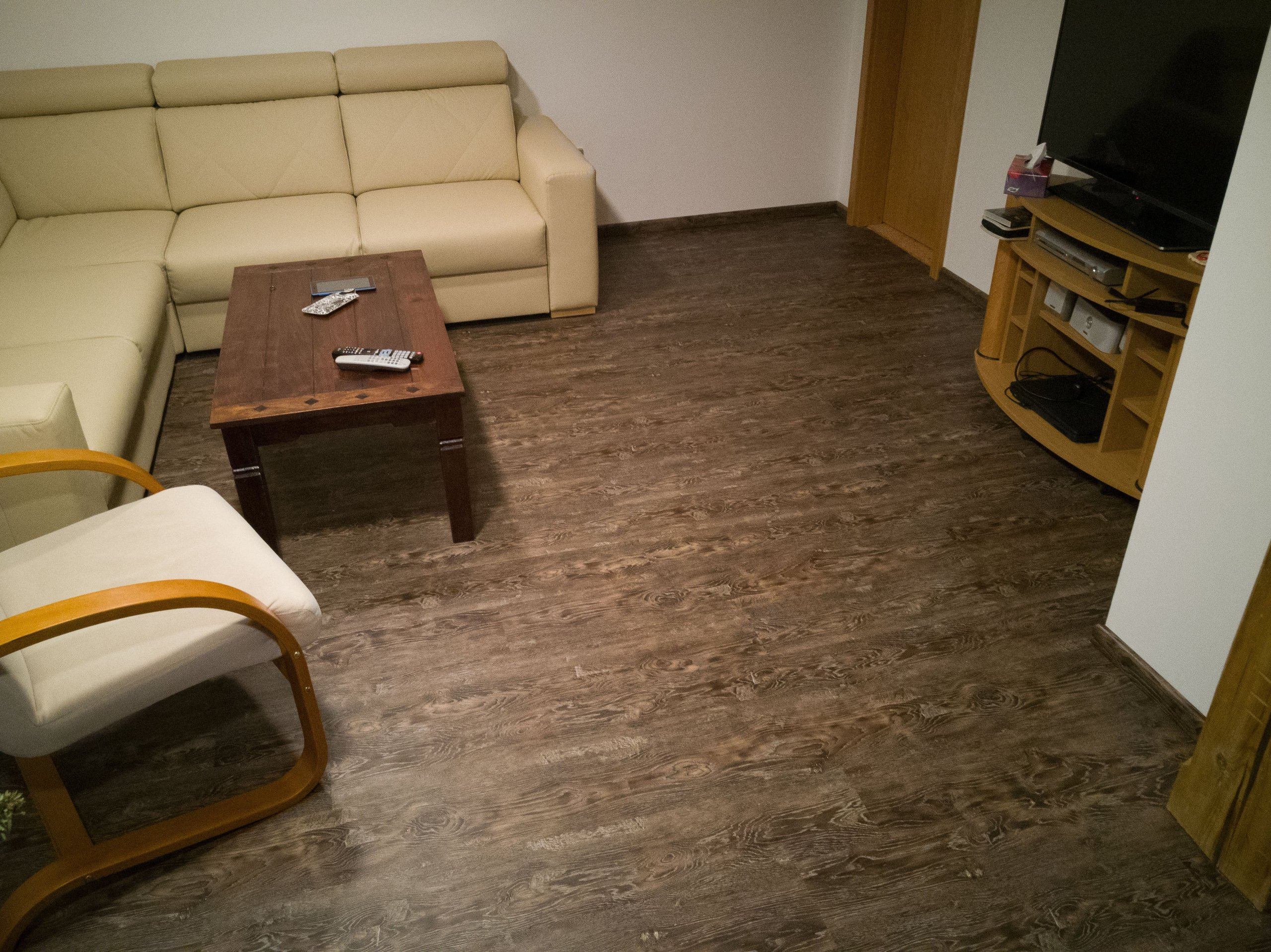 V obývacím pokoji je tmavší dekor podlahy doplněn světlejší sedací soupravou.