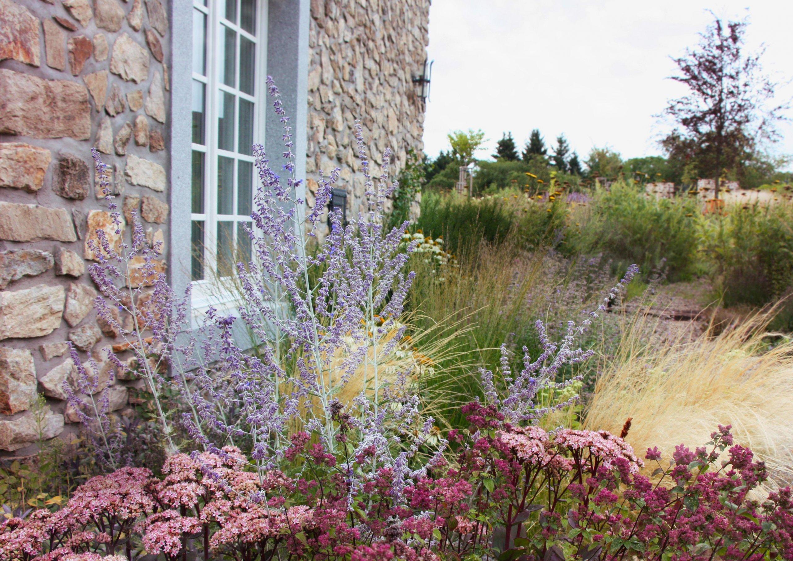Trvalkové záhony jsou v kontrastu s kamenným pozadím domu.