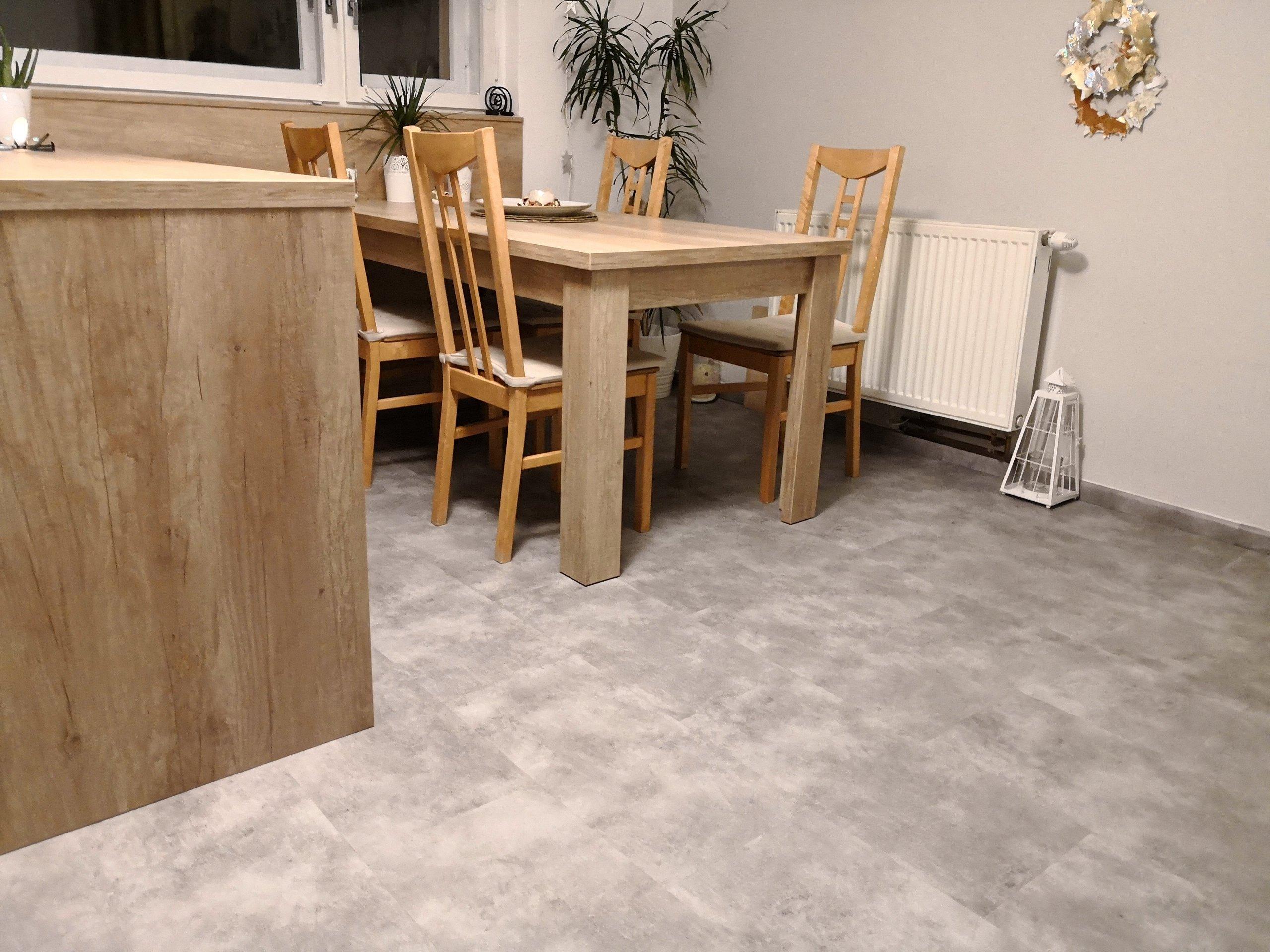 Šedý dekor na podlaze je vkusně doplněn prvky s dekorem dřeva.