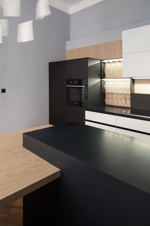 Moderní kuchyně citlivě korespondující s bytem v historickém domě v Královských Vinohradech. Použity byly materiály jako: černý Corian, bělená dubová dýha.…