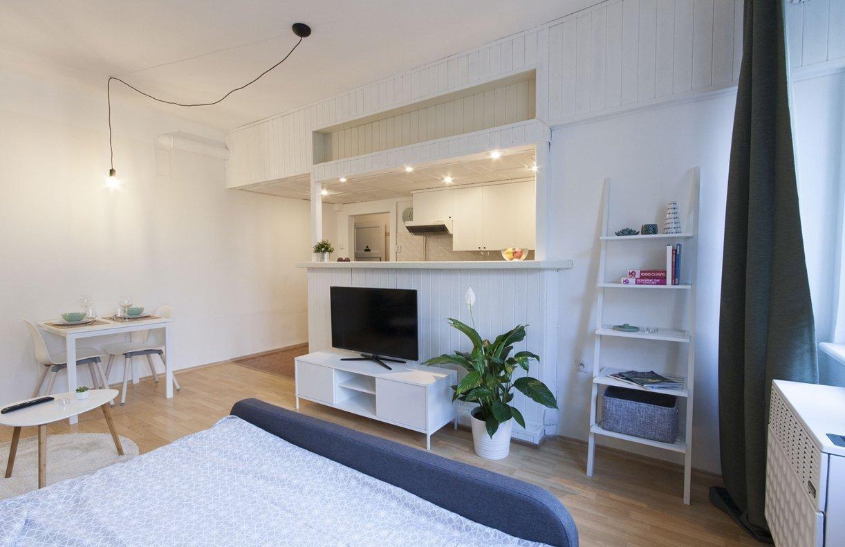 Pohled ze spací části na kuchyň a renovované palubkové obklady
