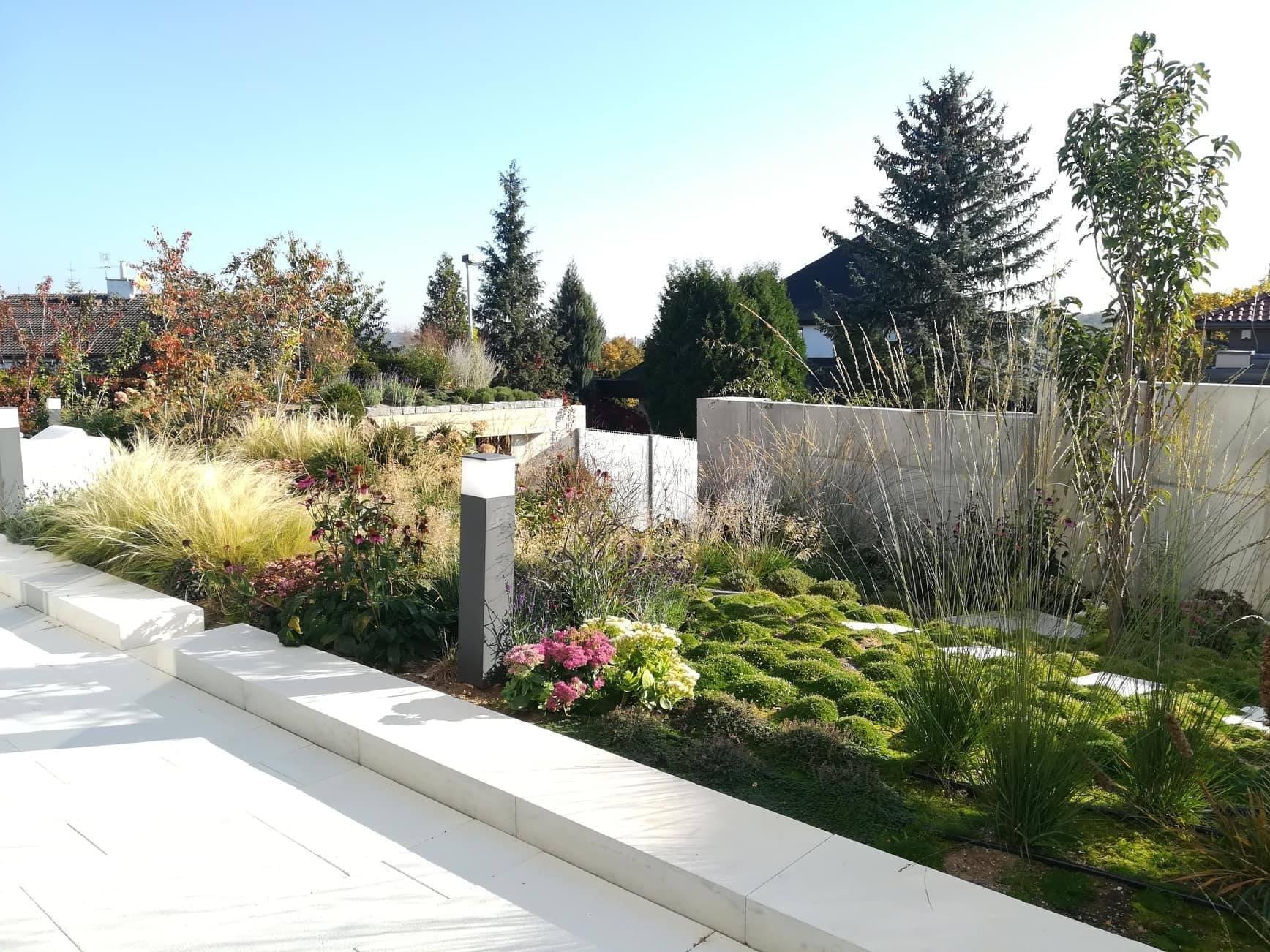 Cílem bylo vytvořit kontrast vertikálních travin a horizontálních zelených koberců. Ty v této části zahrady plně nahradí trávník.