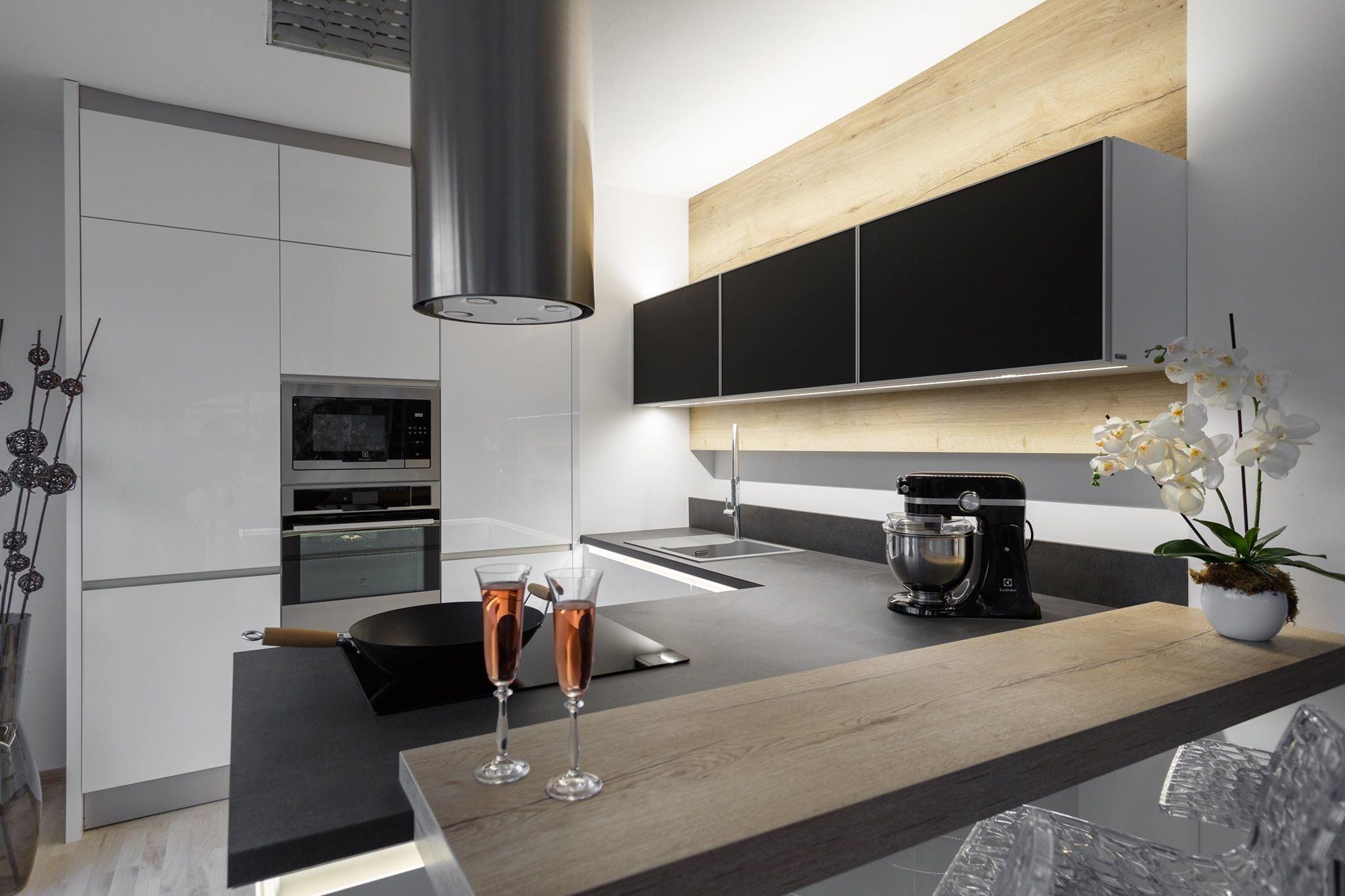 Chytré Kuchyně - bílý lesk s výraznou černou pracovní deskou a nadčasovým dřevodekorem s neparavidelnou kresbou.