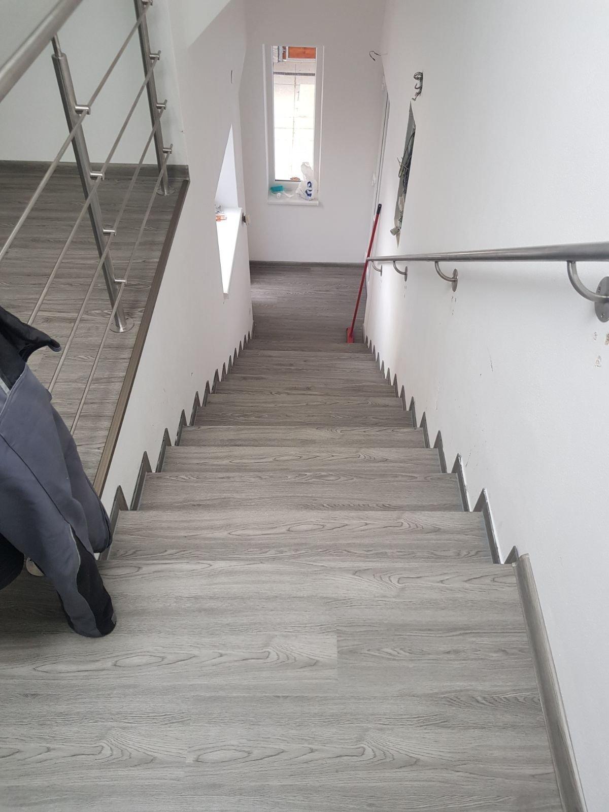 Schodiště z vinylové podlahy, hrany schodů jsou řešeny ohnutým podlahovým dílcem bez kovových lišt.