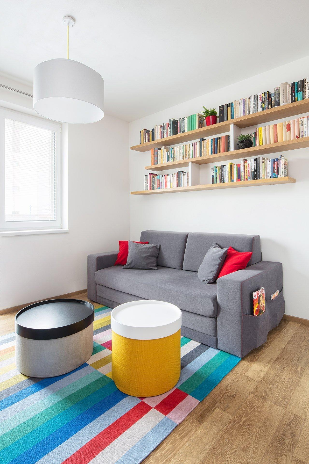 Obývací část oživují jednoduché police plné knih a barevný koberec s víceúčelovými taburety.