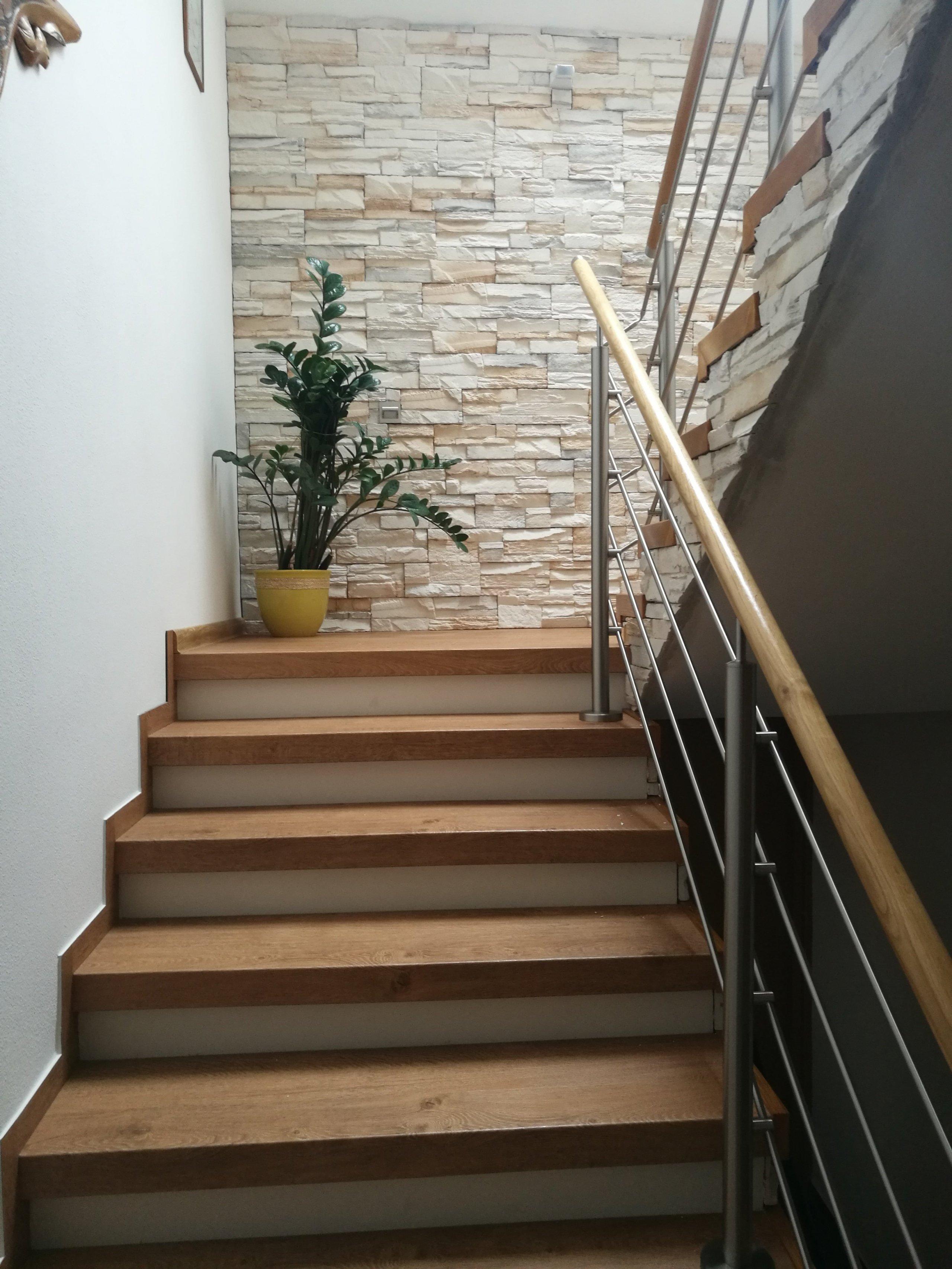 Obklad z umělého kamene hezky ladí s dekorem vinylové podlahy Bukoma na schodových nášlapech