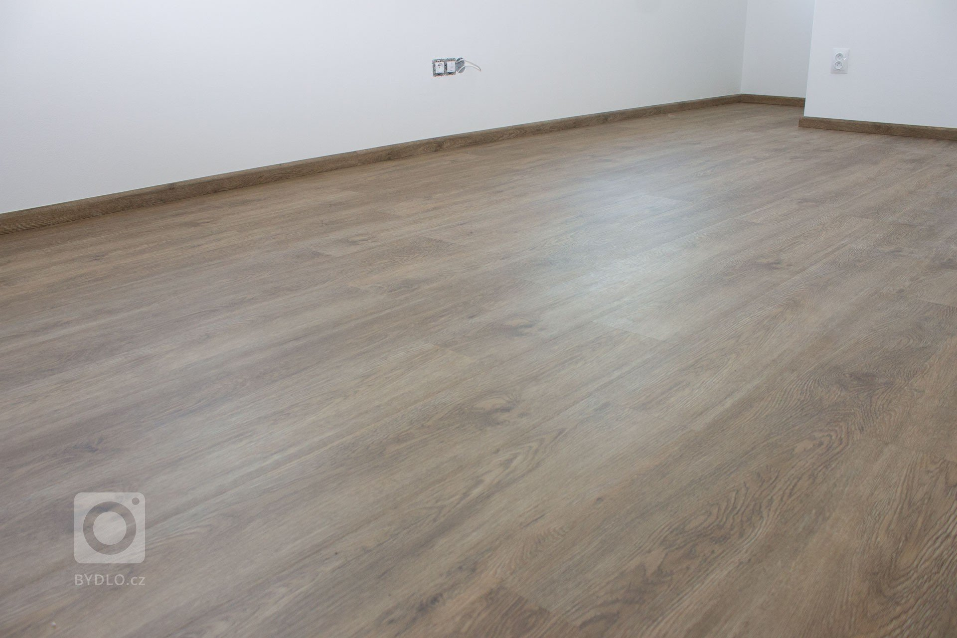 Místnost s vinylovou podlahou BUKOMA CLICK dekor dub Silesia a soklové lišty BUKOMA PROFI-60 s přesným dekorem podlahy
