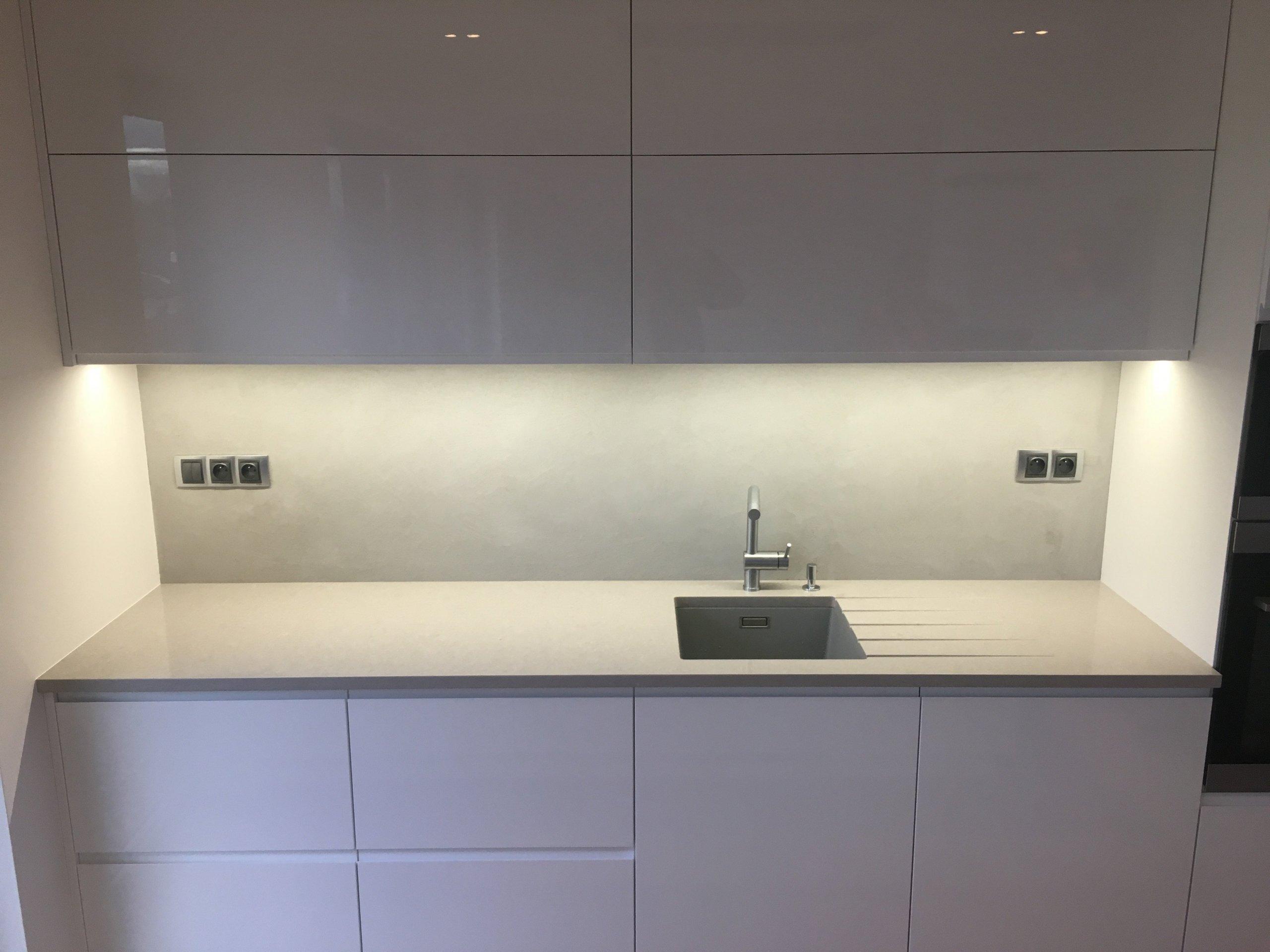 Světle šedá betonová stěrka v rodinném domě na stěnách v obývacím pokoji a za kuchyňskou linkou