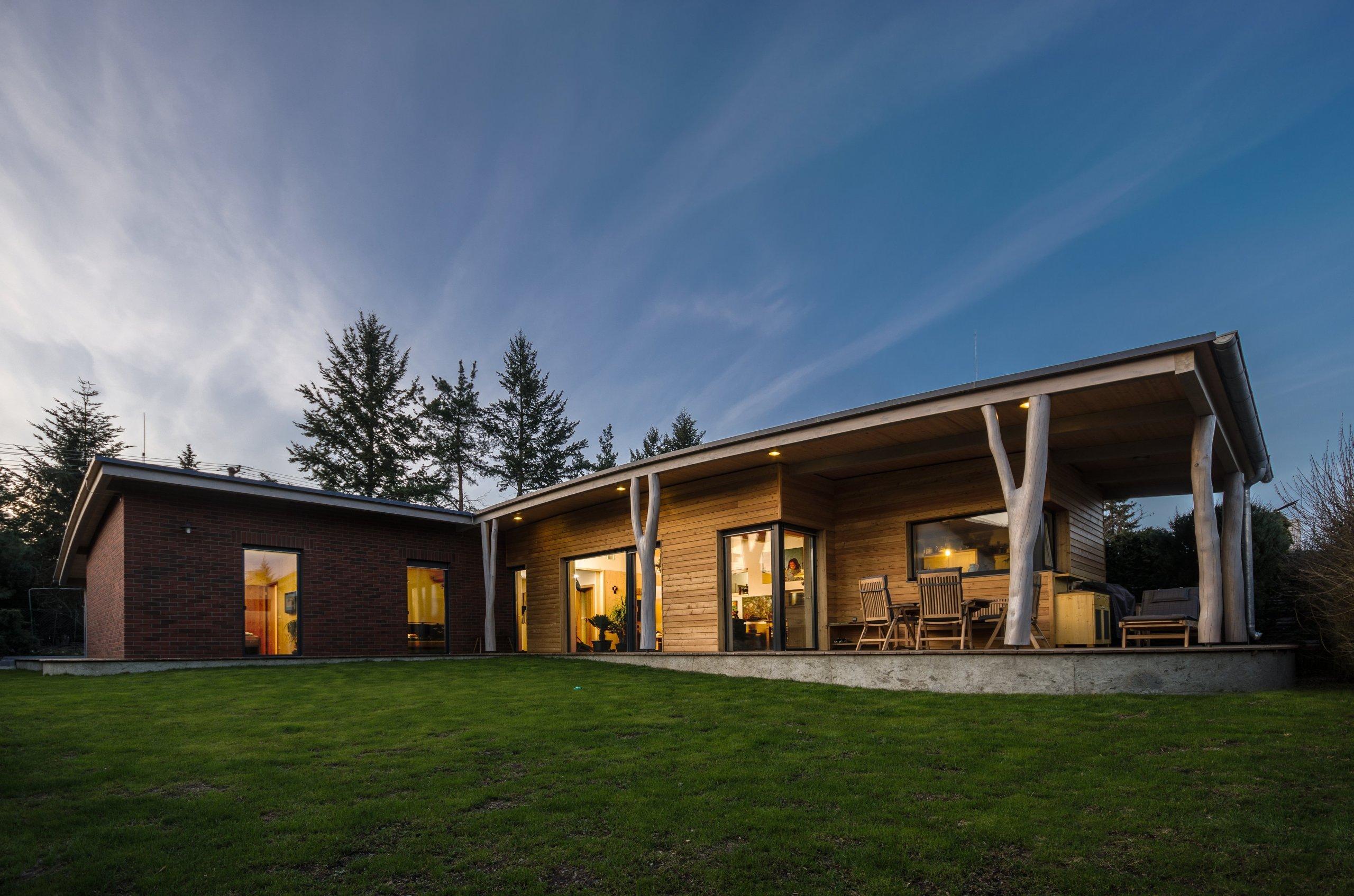"""Jedná se o jednoduchý přízemní dům o půdorysném tvaru """"L"""". Obě ramena domu se otevírají směrem do zahrady. Z kratšího ramene vystupuje kuchyně,…"""