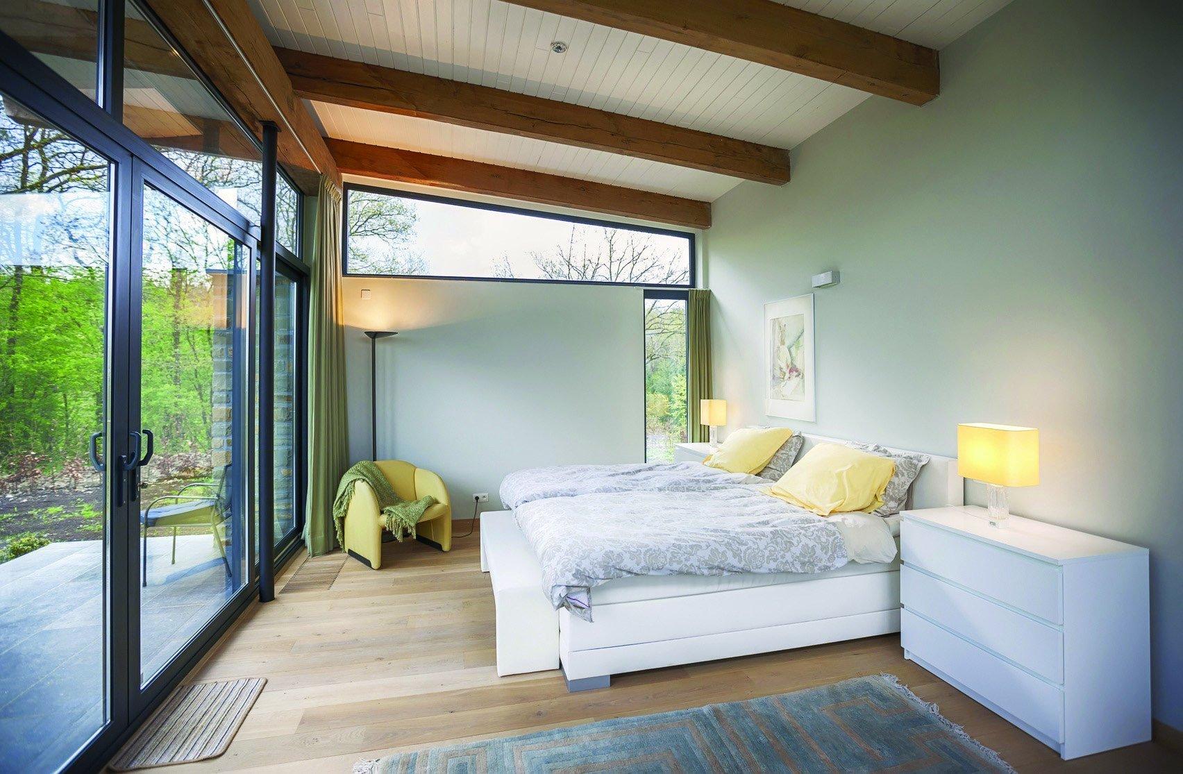Ložnice s prosklenou zdí a dřevěným stropem.